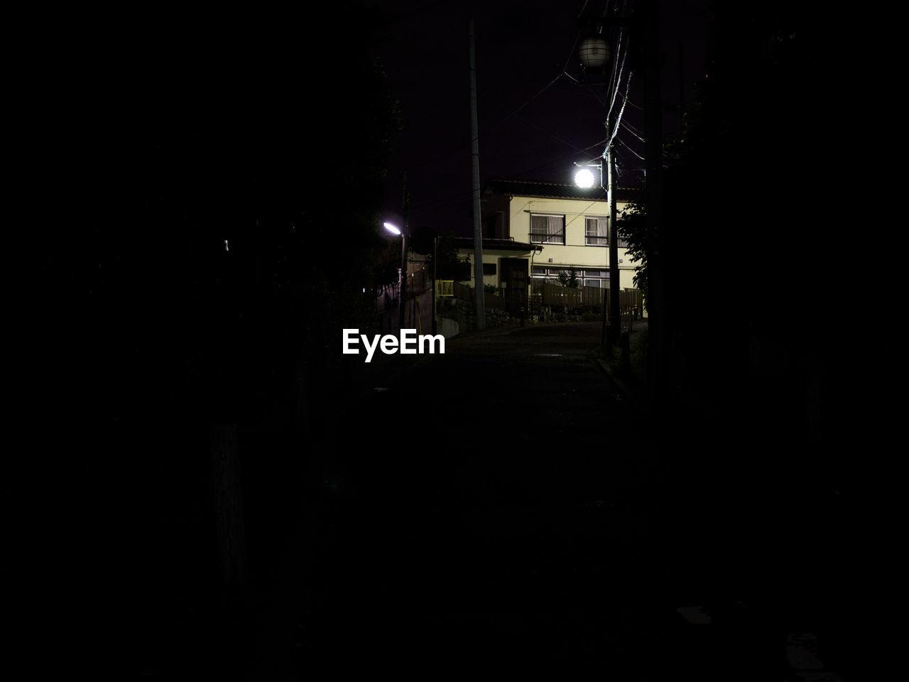 EMPTY ROAD ALONG ILLUMINATED HOUSE AT NIGHT