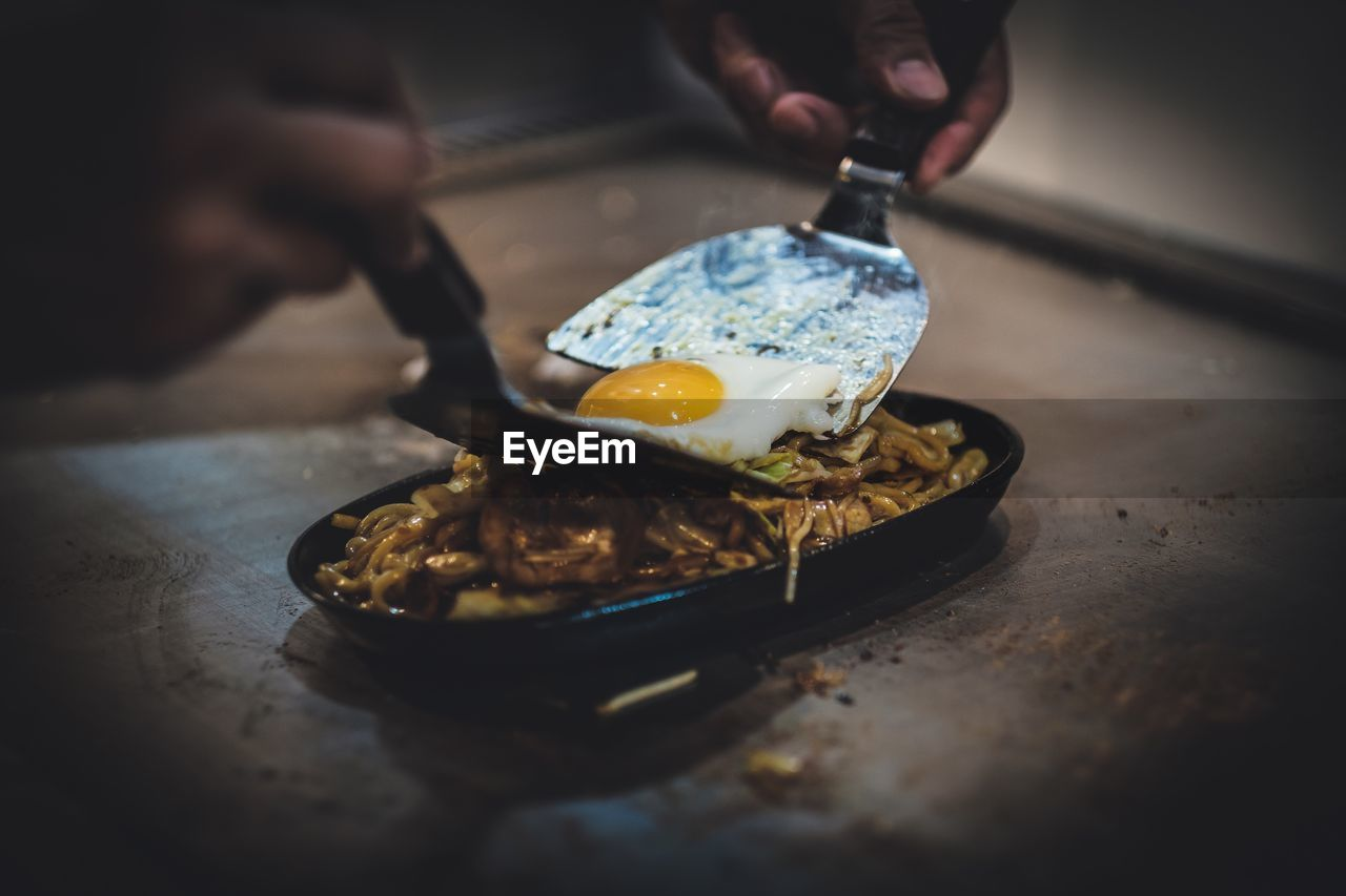 food, food and drink, one person, human hand, real people, holding, indoors, selective focus, hand, freshness, human body part, unrecognizable person, table, preparation, ready-to-eat, close-up, men, lifestyles, eating, preparing food, finger, street food, chef, temptation