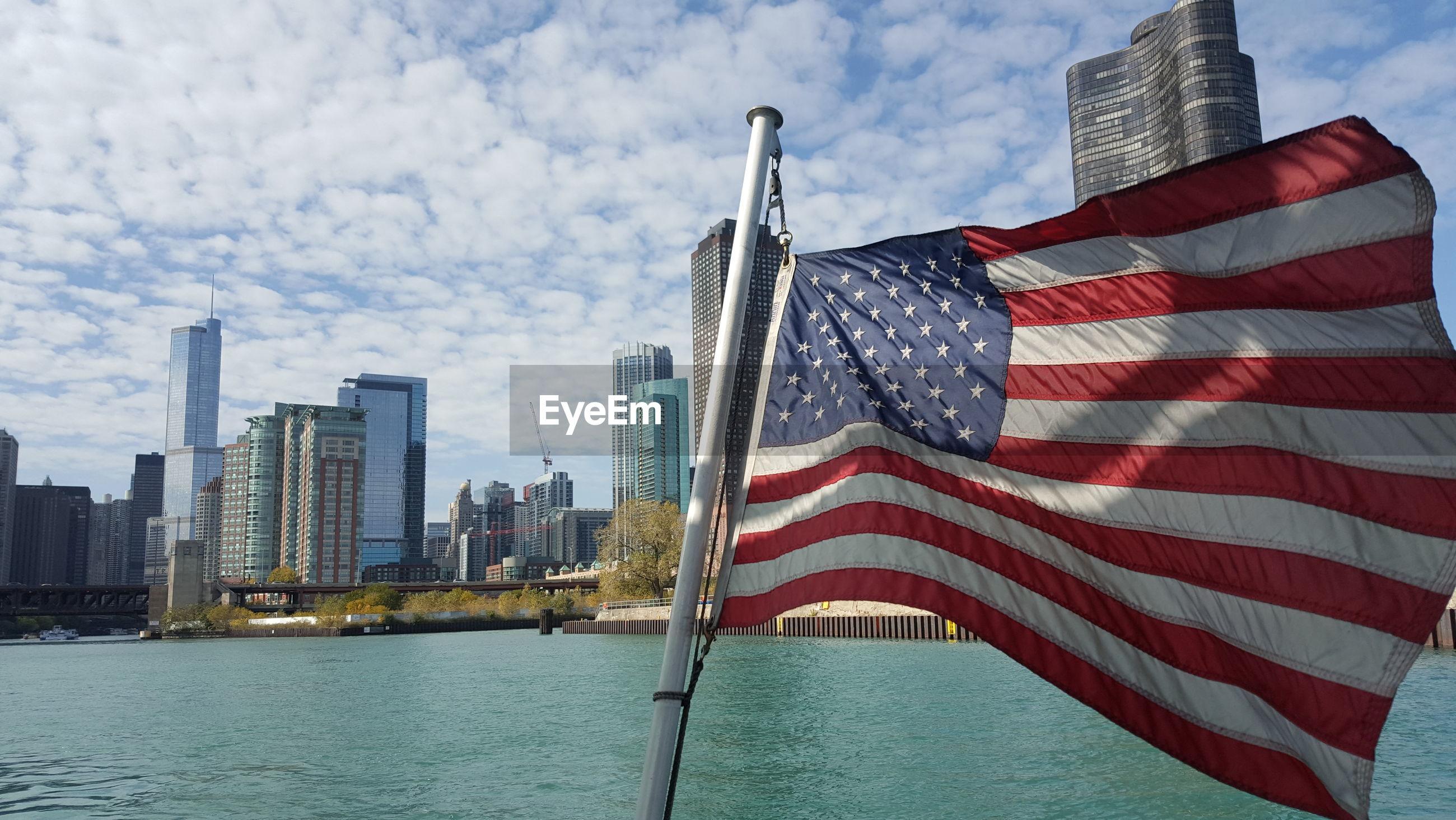 FLAG AGAINST SKY IN CITY SKYLINE AGAINST CLOUDY DAY