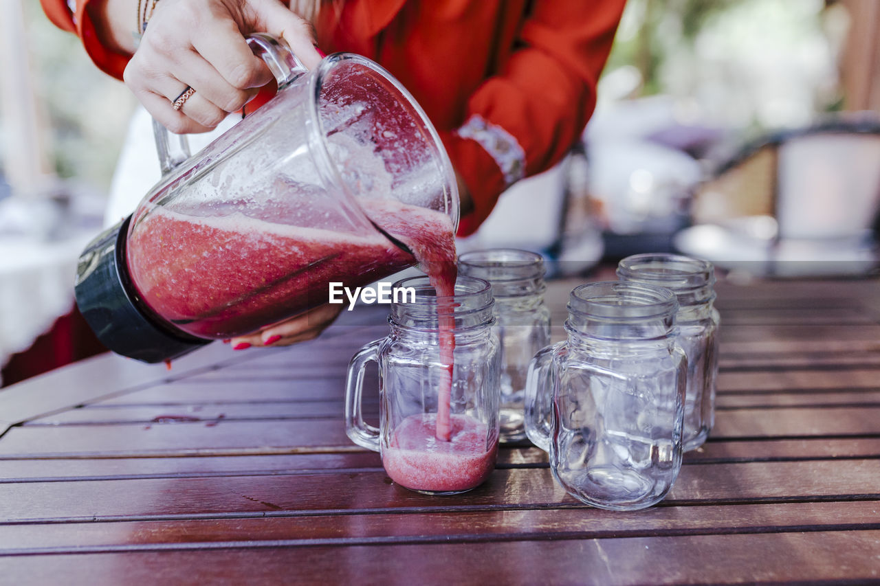 food and drink, one person, glass - material, focus on foreground, transparent, real people, table, glass, indoors, human hand, hand, holding, close-up, container, drinking glass, freshness, household equipment, bottle, pouring