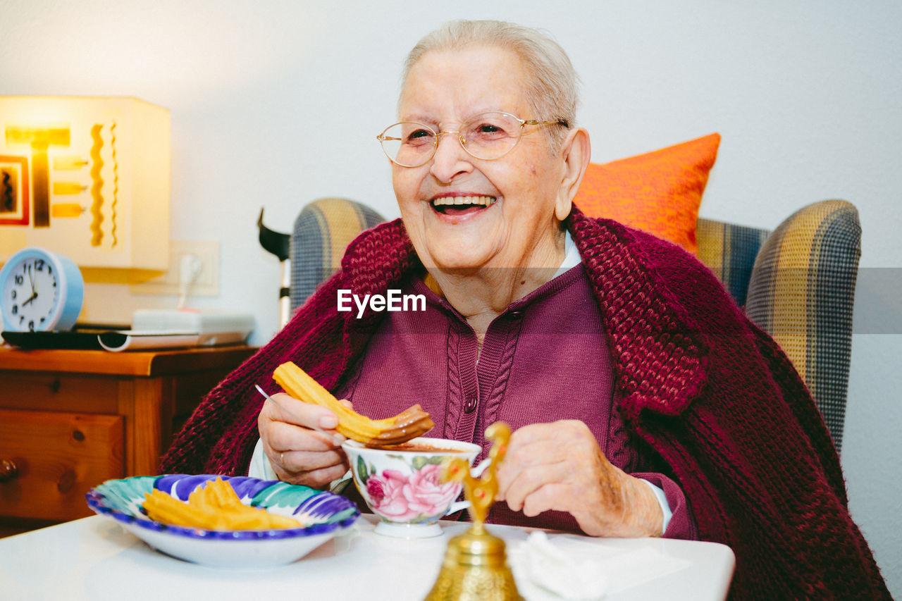 Portrait Of Senior Woman Eating Churros