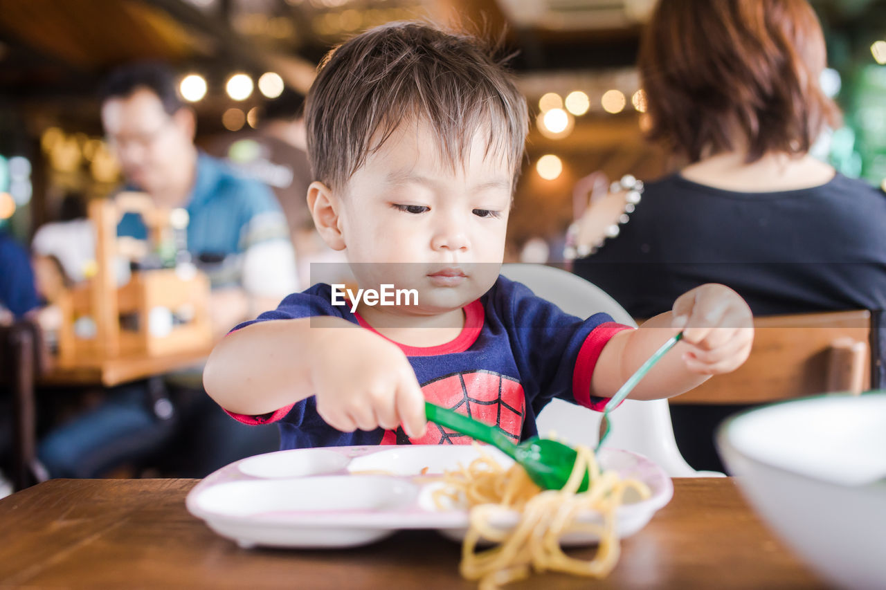 Close-Up Of Boy Eating Noodles On Table At Restaurant
