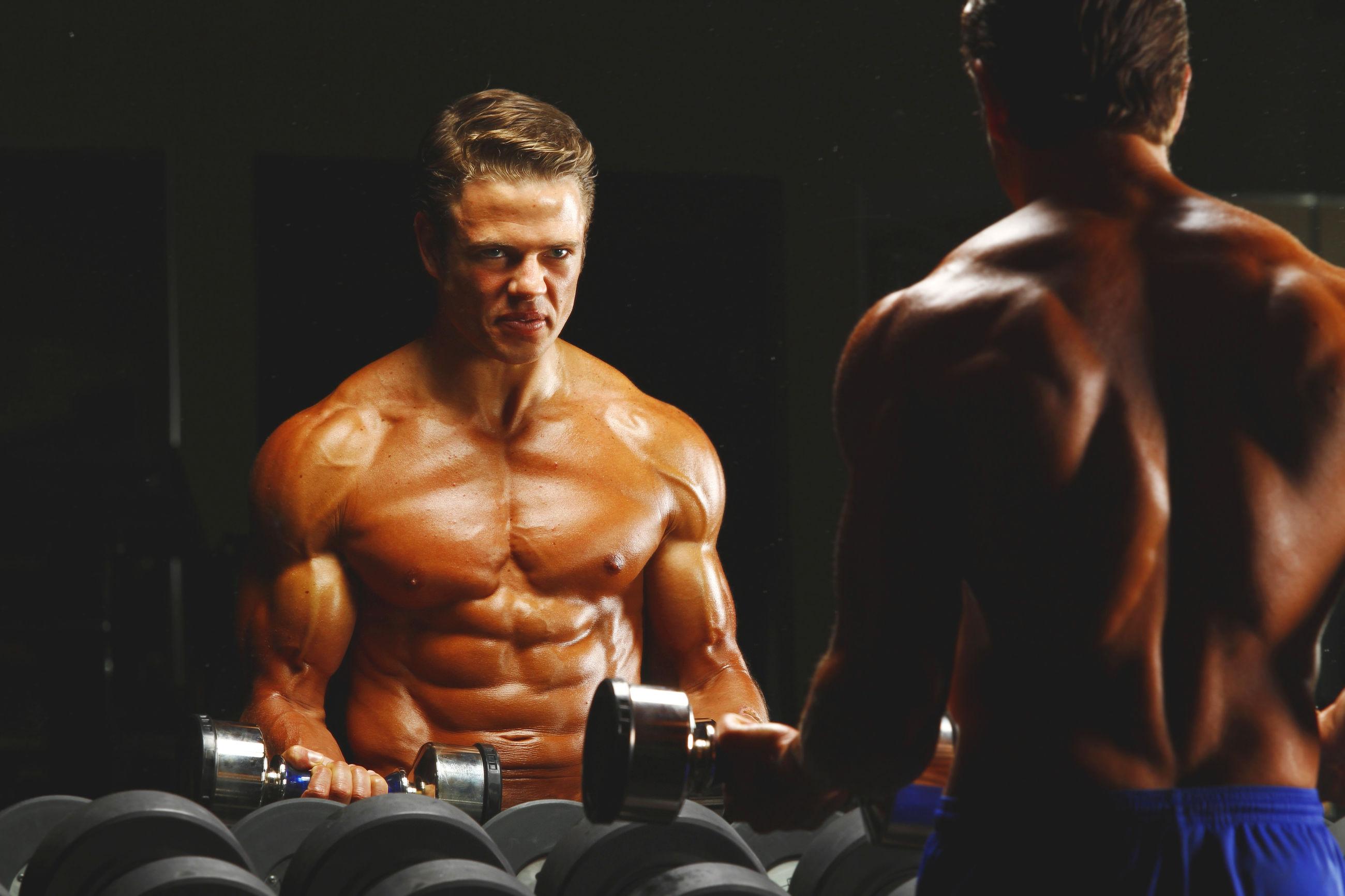 Shirtless muscular man exercising in gym