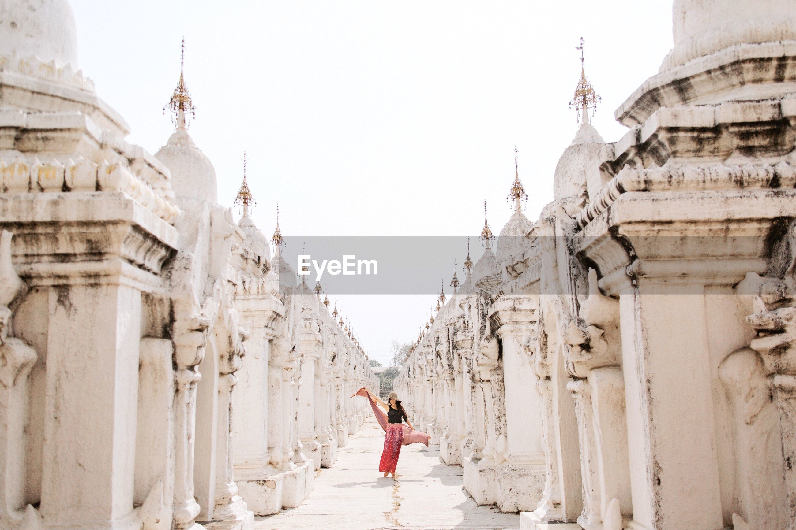 Woman standing outside temple against clear sky