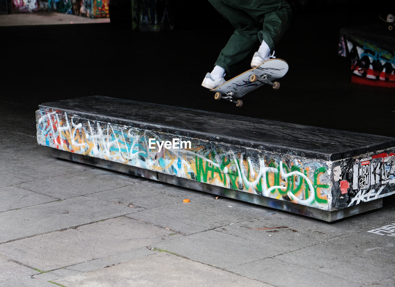 LOW SECTION OF PERSON SKATEBOARDING ON SKATEBOARD
