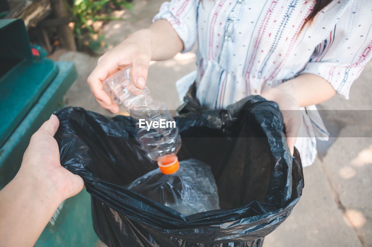 Midsection Of Woman Putting Plastic Bottle In Bag