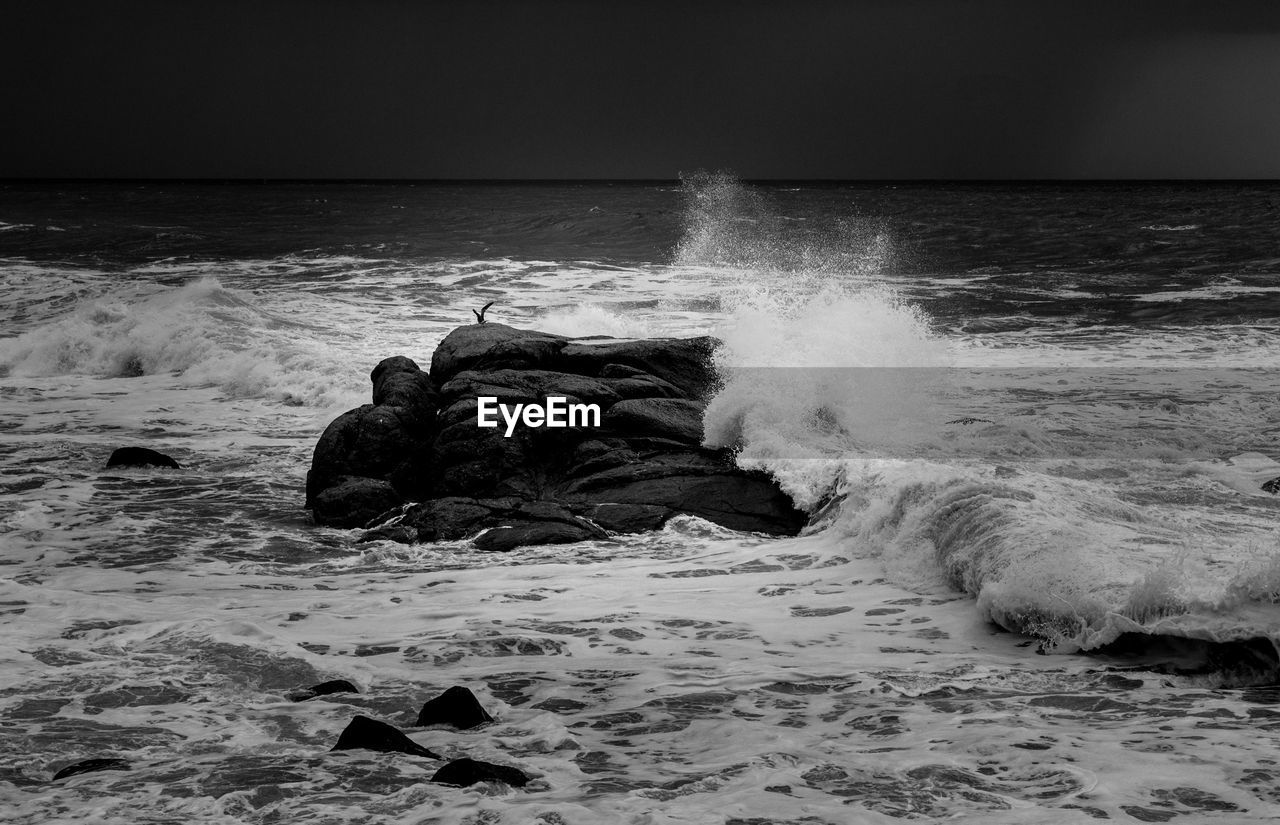 Wave splashing on rock in sea against sky