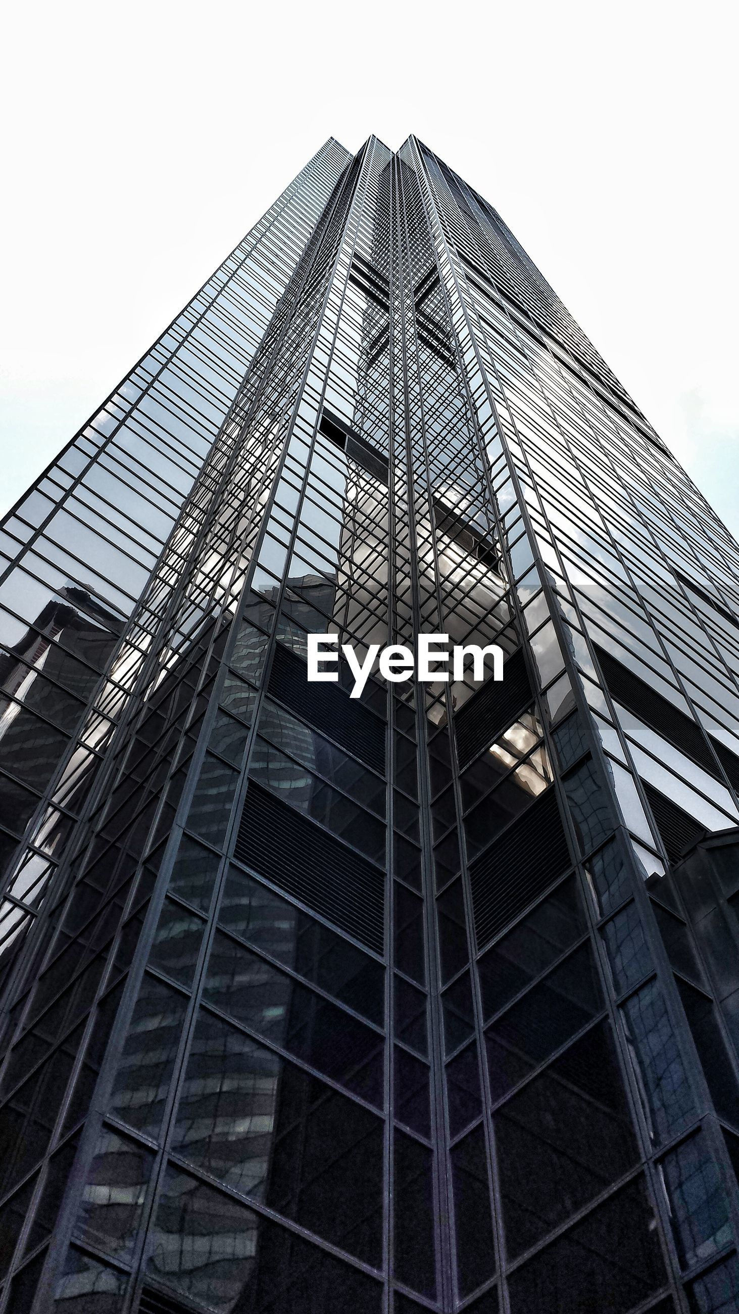 low angle view, architecture, built structure, building exterior, modern, office building, tall - high, city, glass - material, skyscraper, tower, building, clear sky, sky, day, outdoors, no people, architectural feature, tall, development