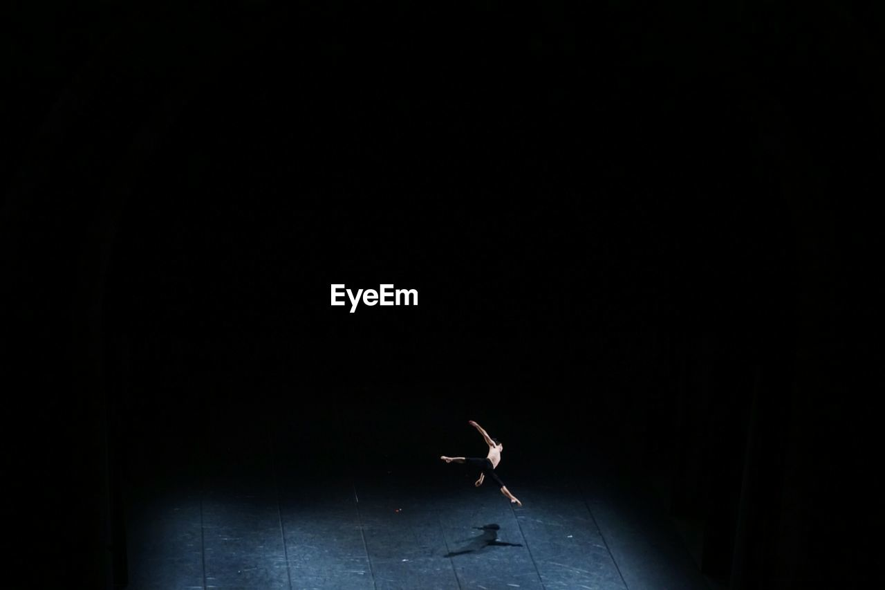 Shirtless man performing ballet dance on stage
