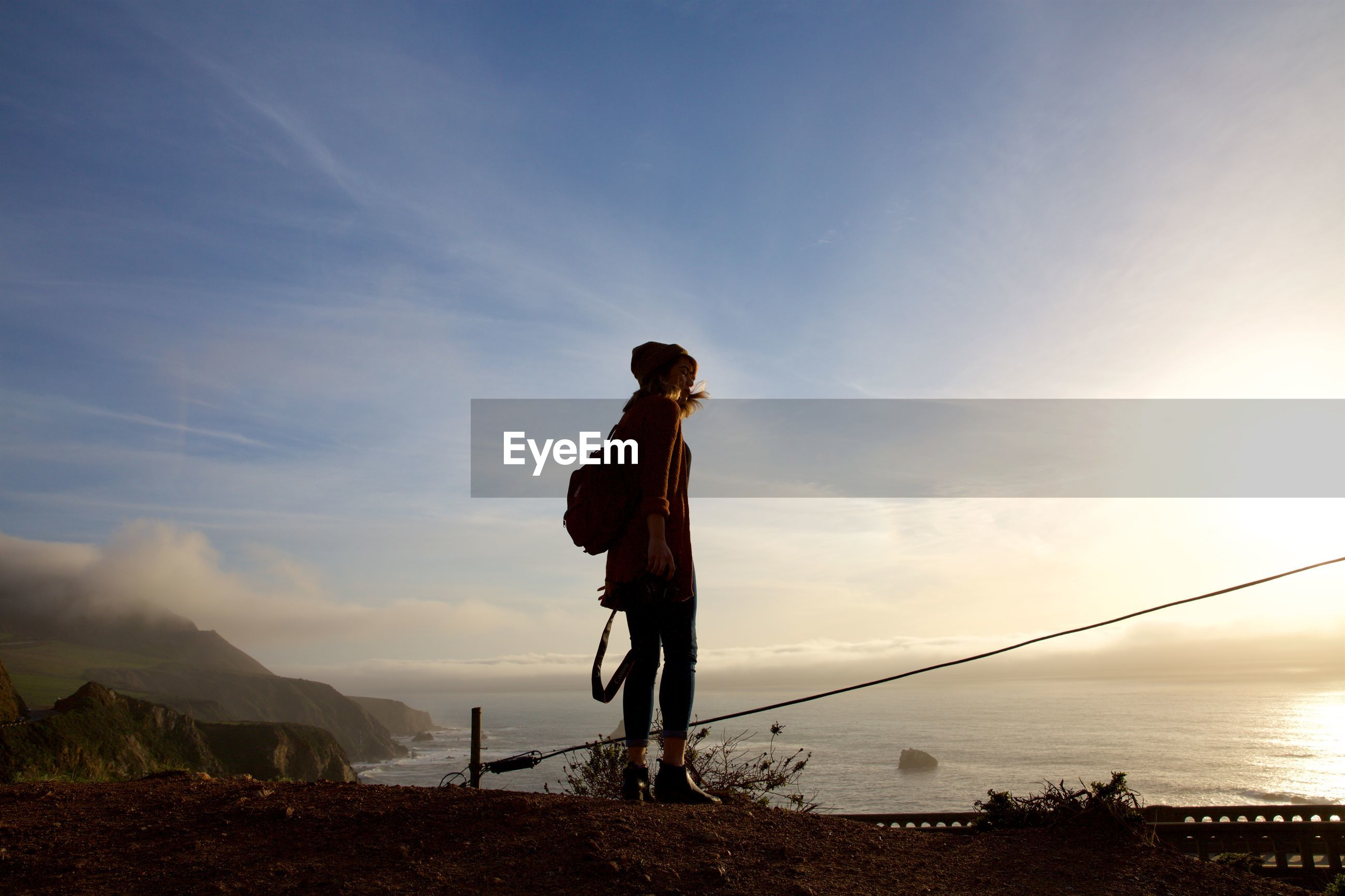 Low angle view of woman standing by sea against sky
