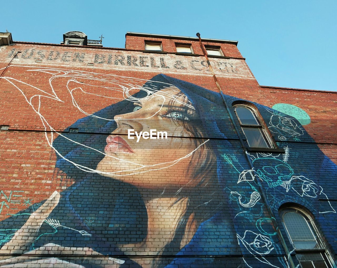 Low angle view of mural on building against sky