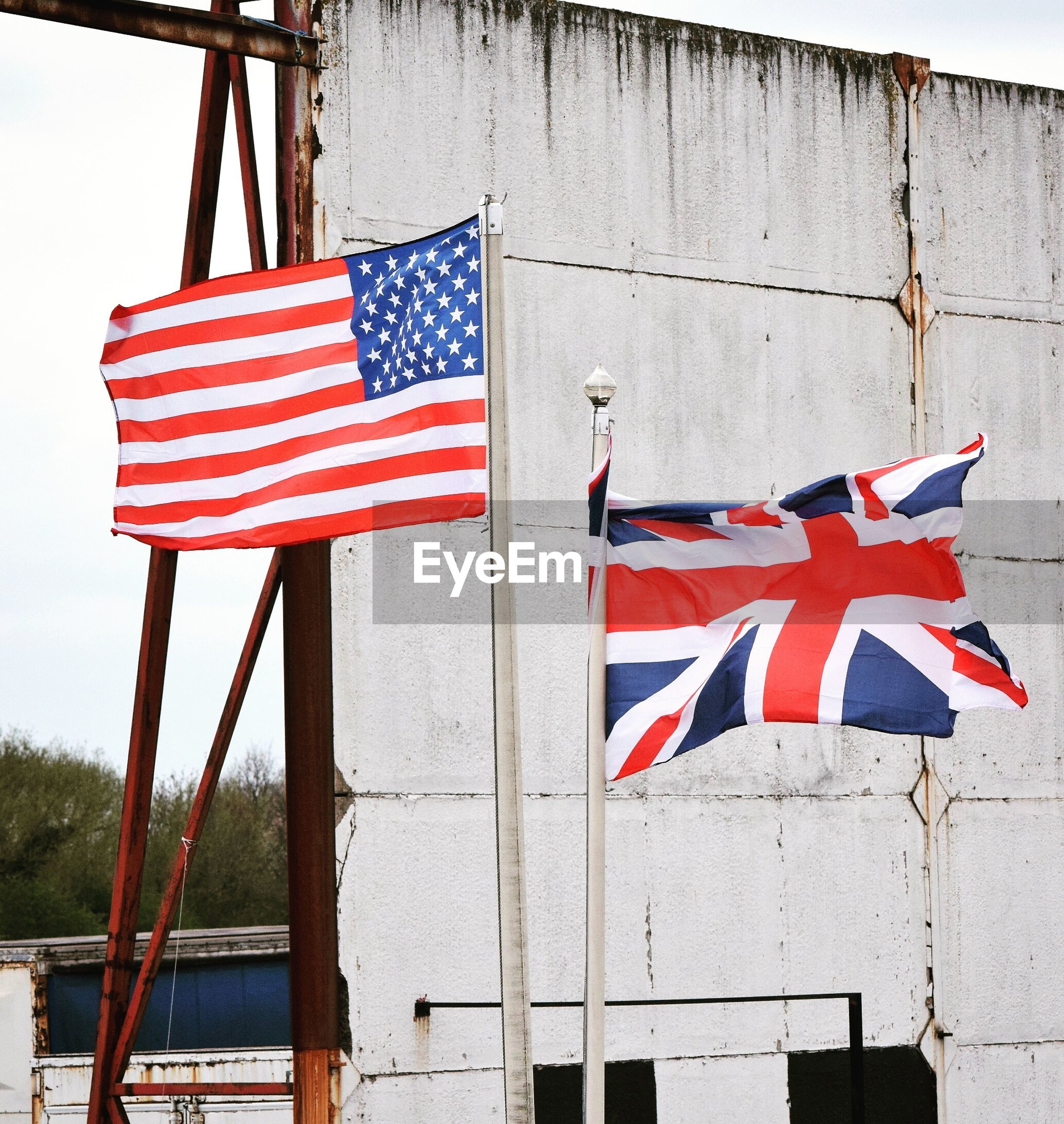 Low angle view of american and british flags against wall
