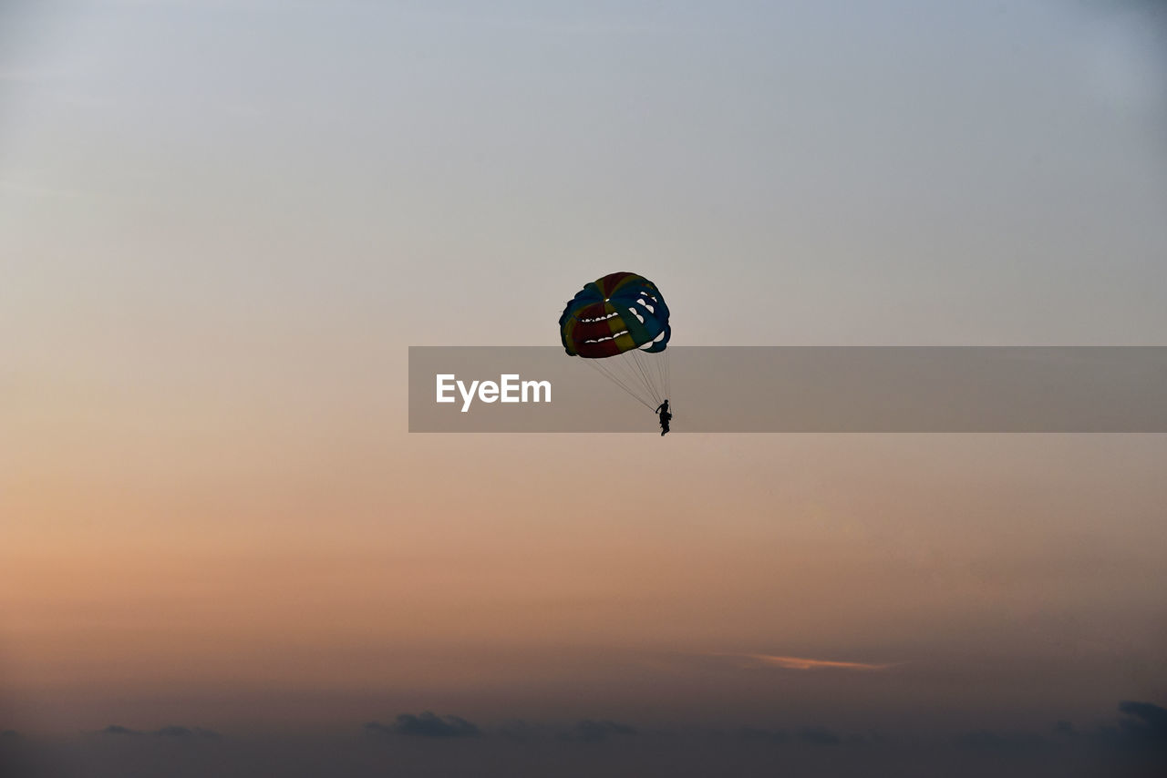 adventure, extreme sports, sky, sunset, sport, mid-air, parachute, paragliding, unrecognizable person, leisure activity, real people, one person, freedom, flying, low angle view, exhilaration, joy, orange color, lifestyles, beauty in nature, parasailing