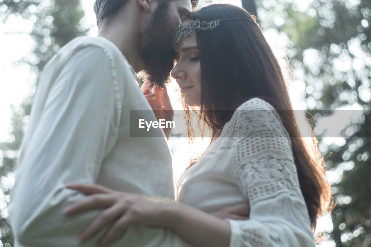 togetherness, young women, young adult, love, two people, emotion, couple - relationship, bonding, real people, lifestyles, positive emotion, women, young men, leisure activity, adult, heterosexual couple, embracing, day, tree, side view, outdoors, hairstyle