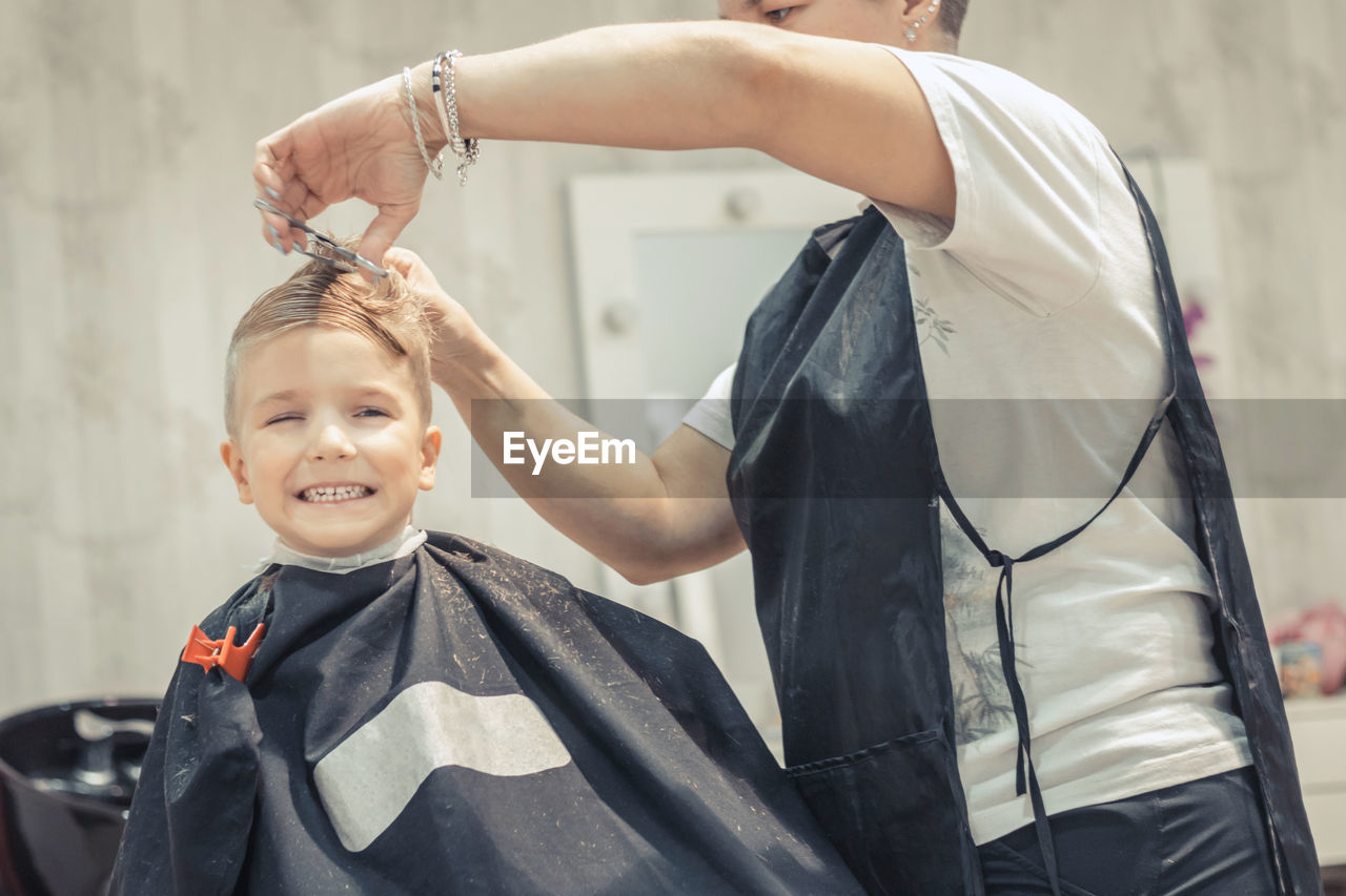 Midsection of barber cutting hair of boy at shop