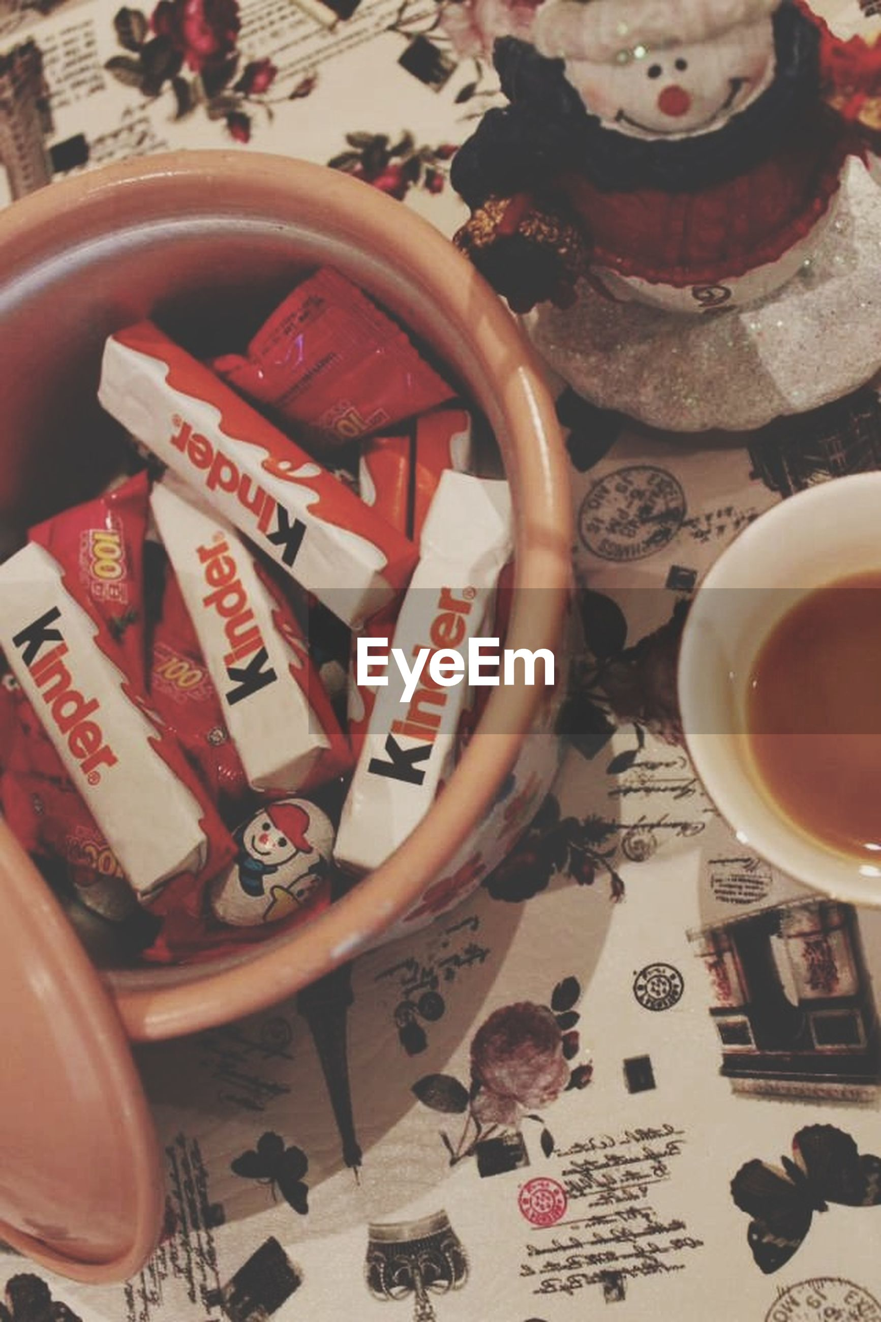 indoors, table, high angle view, still life, text, communication, coffee cup, no people, food and drink, container, home interior, cup, day, bowl, variation, art, animal representation, western script, close-up, toy