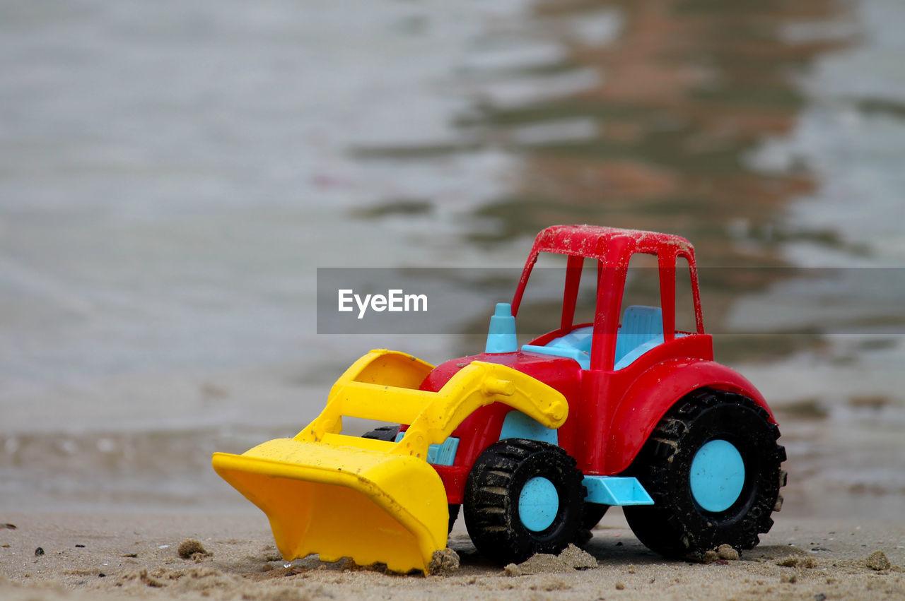 Toy Excavator At Lakeshore