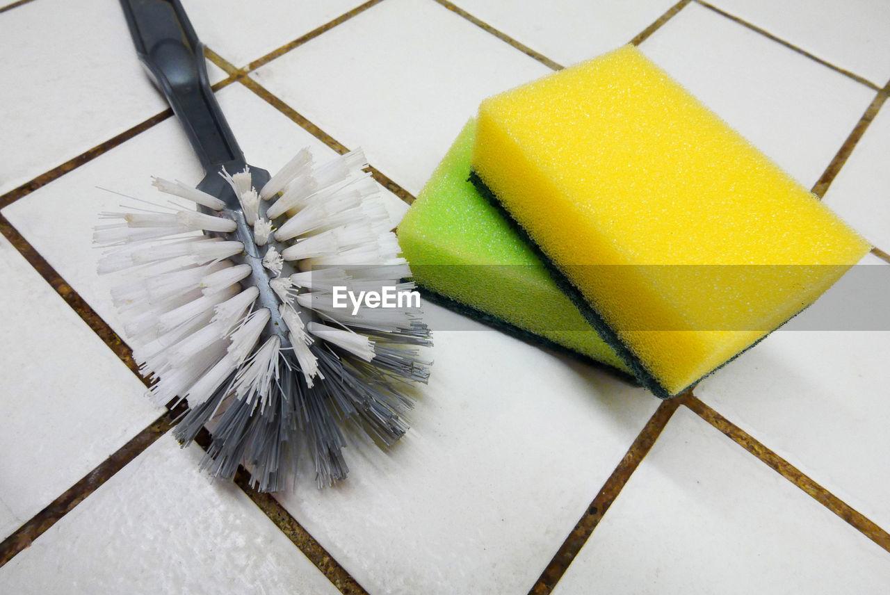 Close-Up Of Brush And Sponge Scrub On Flooring