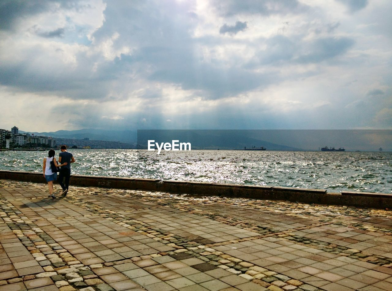 cloud - sky, sky, water, real people, lifestyles, sea, people, nature, full length, women, adult, leisure activity, men, stone, rear view, outdoors, day, beauty in nature, paving stone, promenade