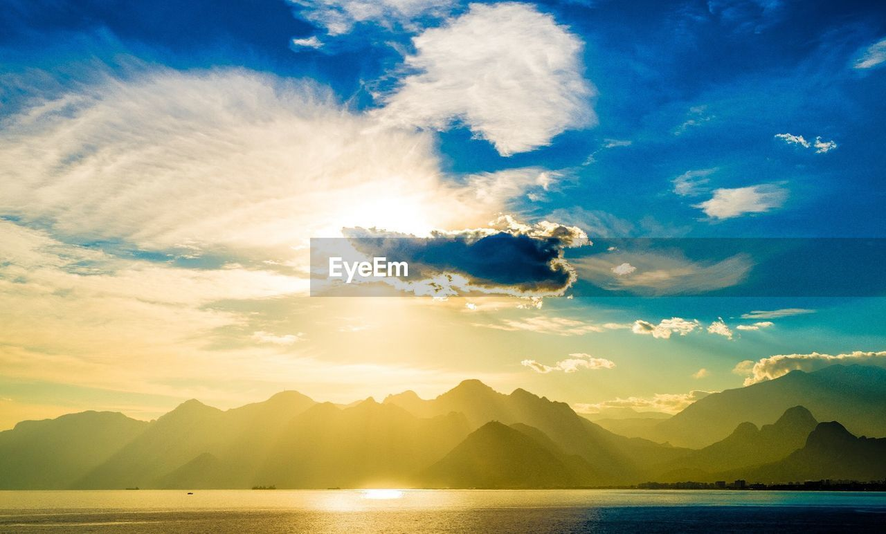 Scenic view of lake by mountains against cloudy sky at sunset