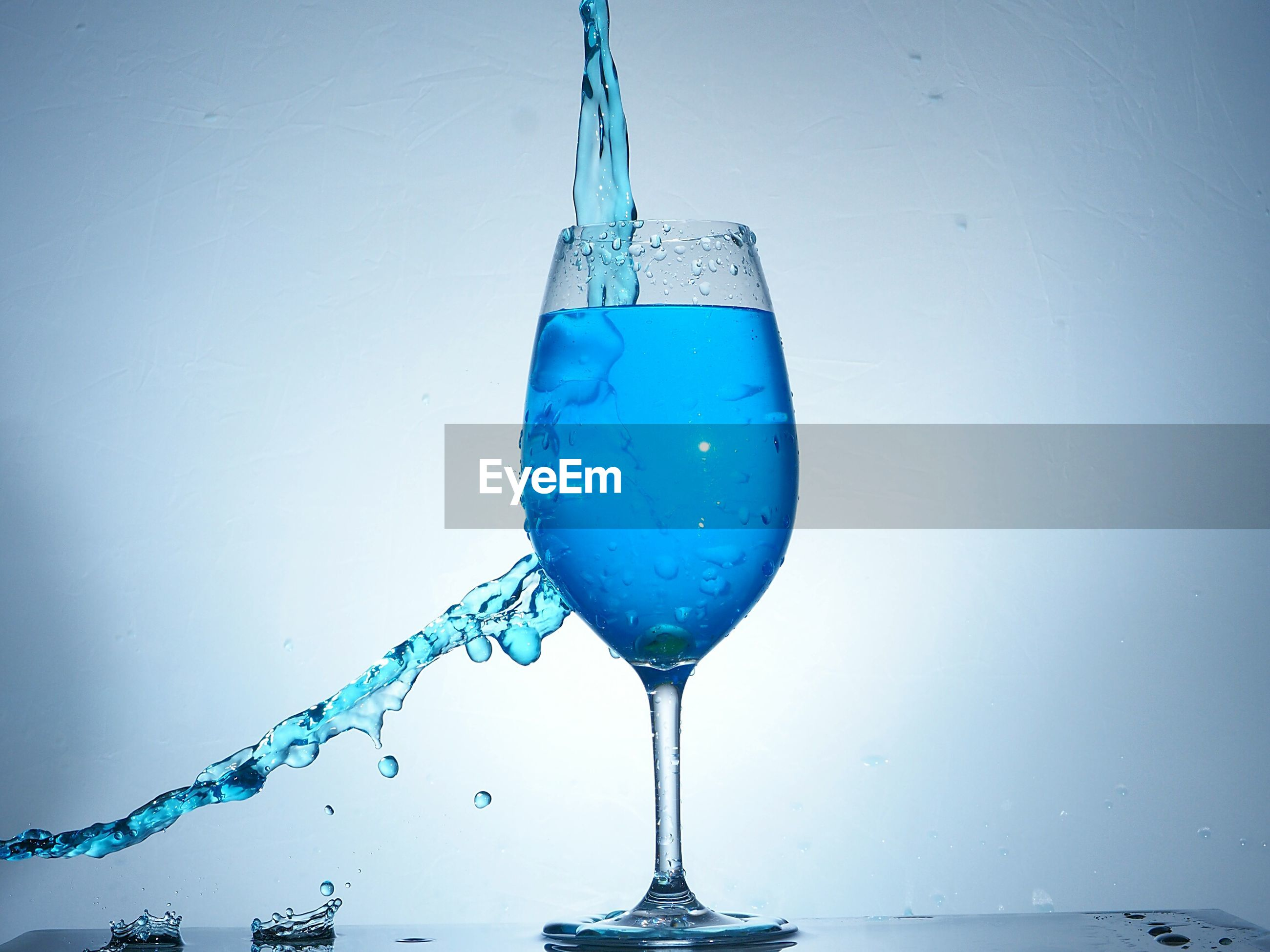 CLOSE-UP OF WATER DROP ON BLUE GLASS AGAINST WHITE BACKGROUND