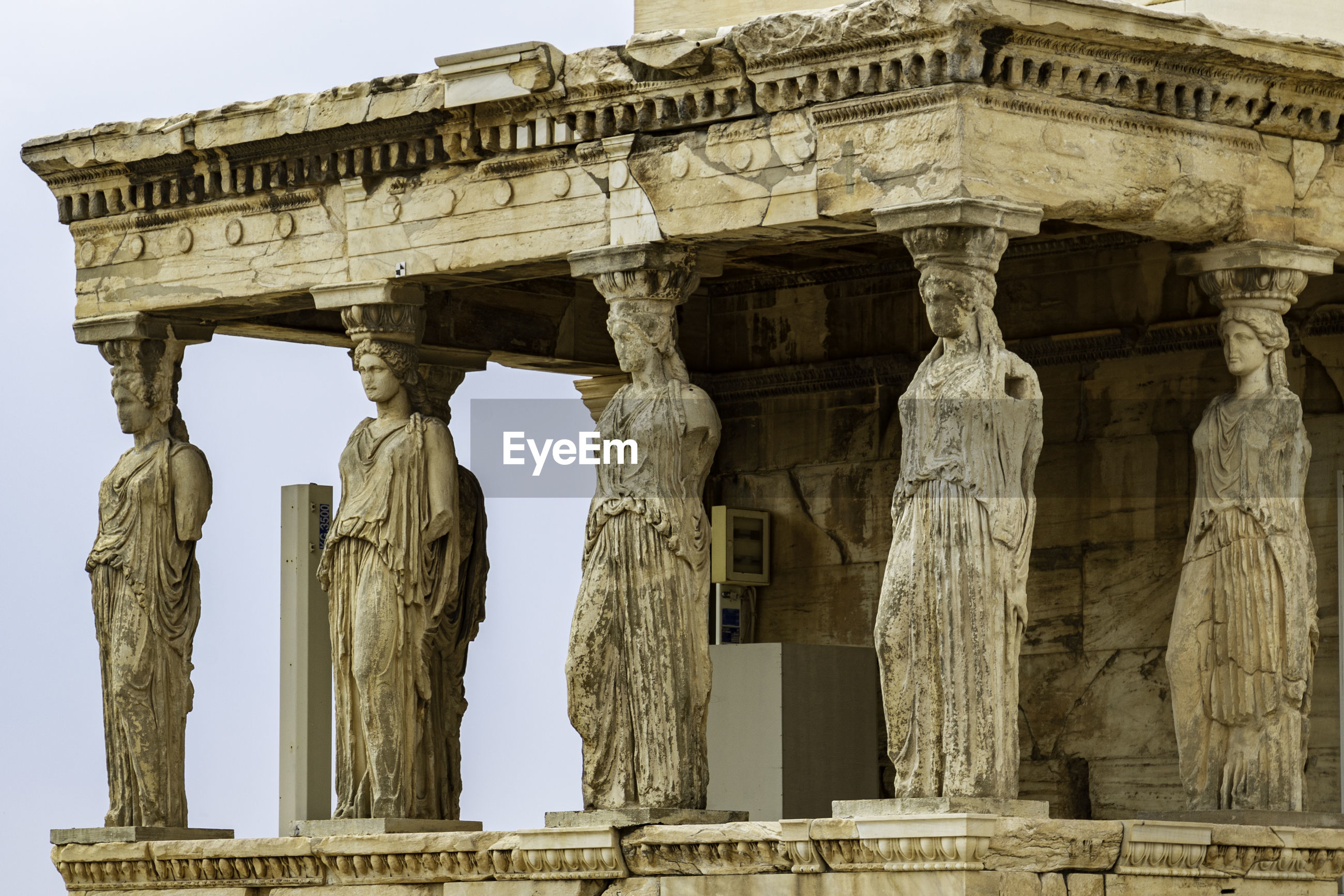 Low angle view of caryatids on acropolis in athens in front of blue sky