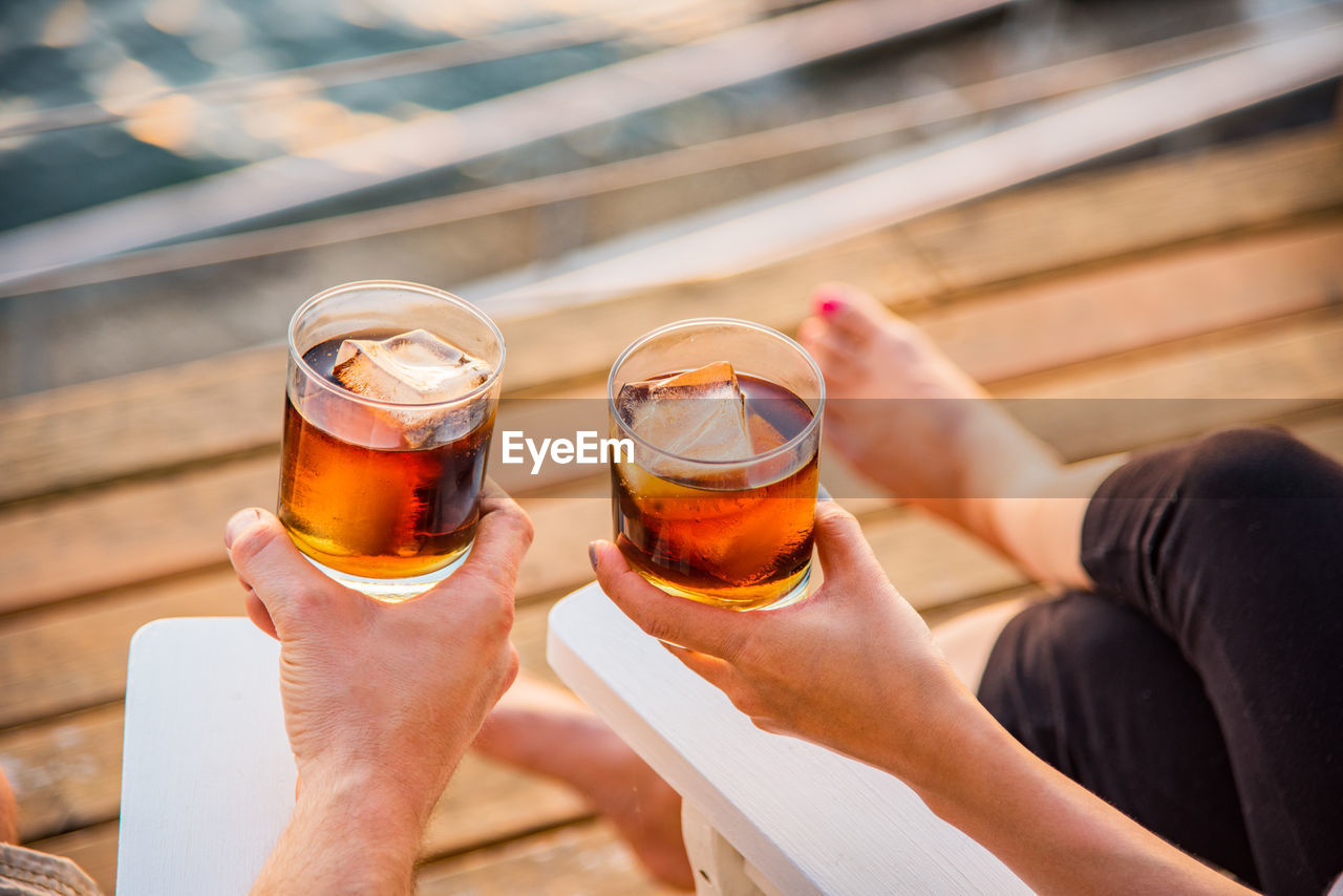 Cropped image of couple holding rum glasses while sitting on dock