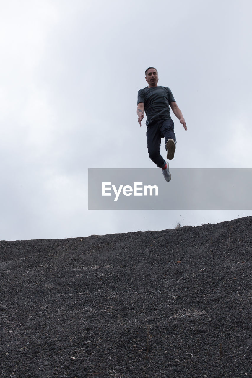 Full length of man jumping on land against cloudy sky