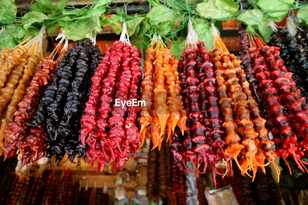 CLOSE-UP OF FRUITS HANGING IN MARKET