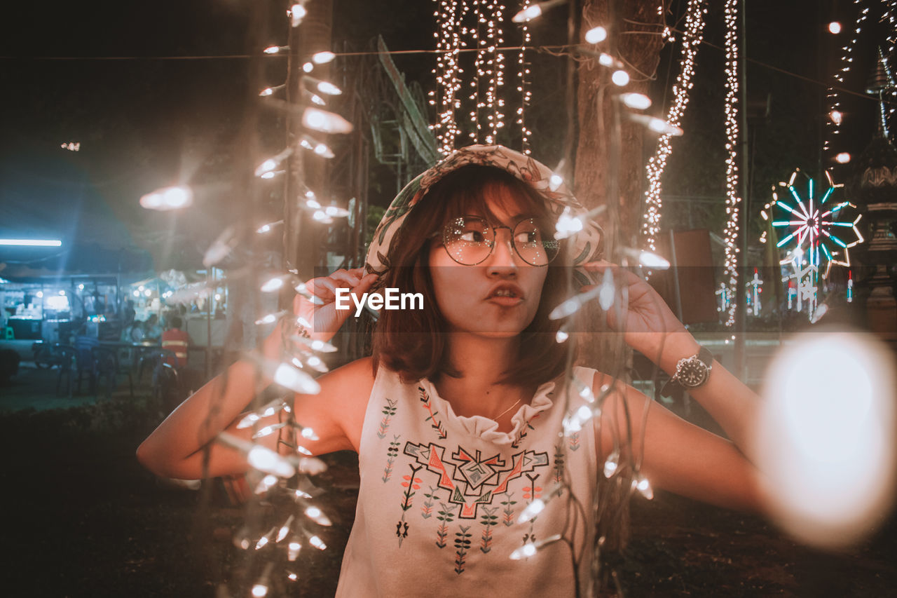 Young woman making face amidst illuminated lights