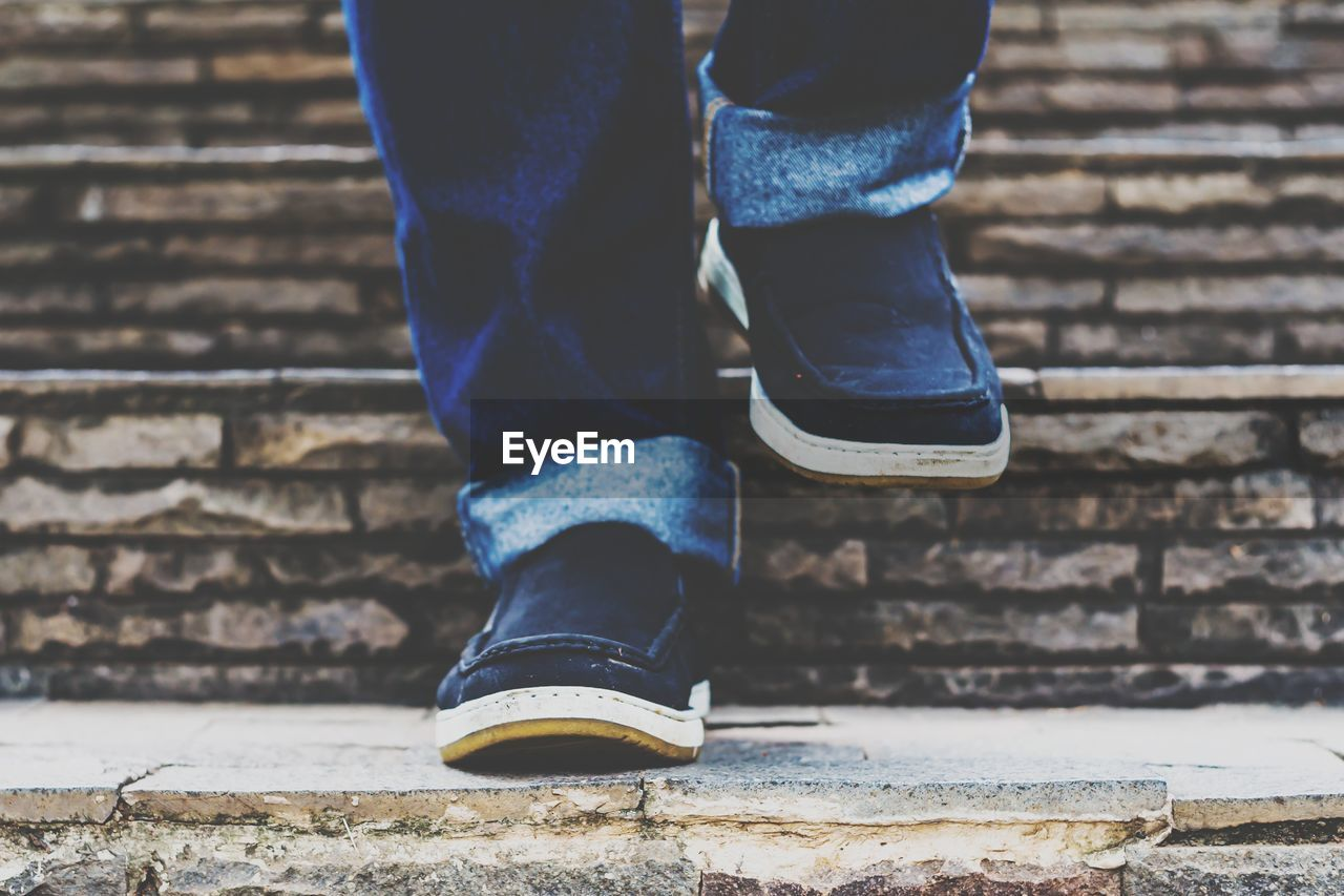 human leg, low section, human body part, body part, one person, shoe, real people, staircase, lifestyles, day, architecture, jeans, standing, outdoors, leisure activity, unrecognizable person, human limb, limb, men, human foot, brick