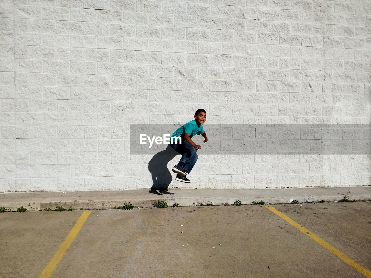 Full Length Of Boy Jumping Against Wall