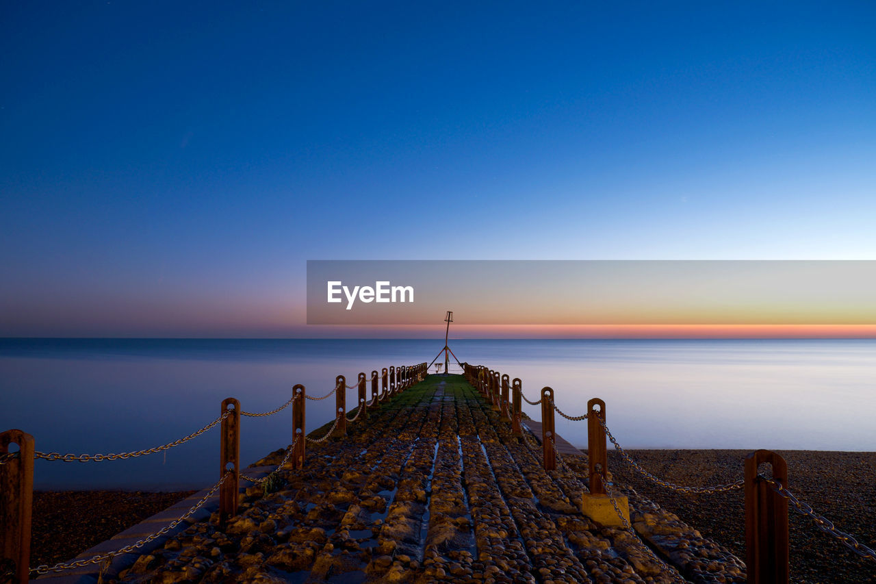 Old Pier At Beach Against Clear Blue Sky At Sunset