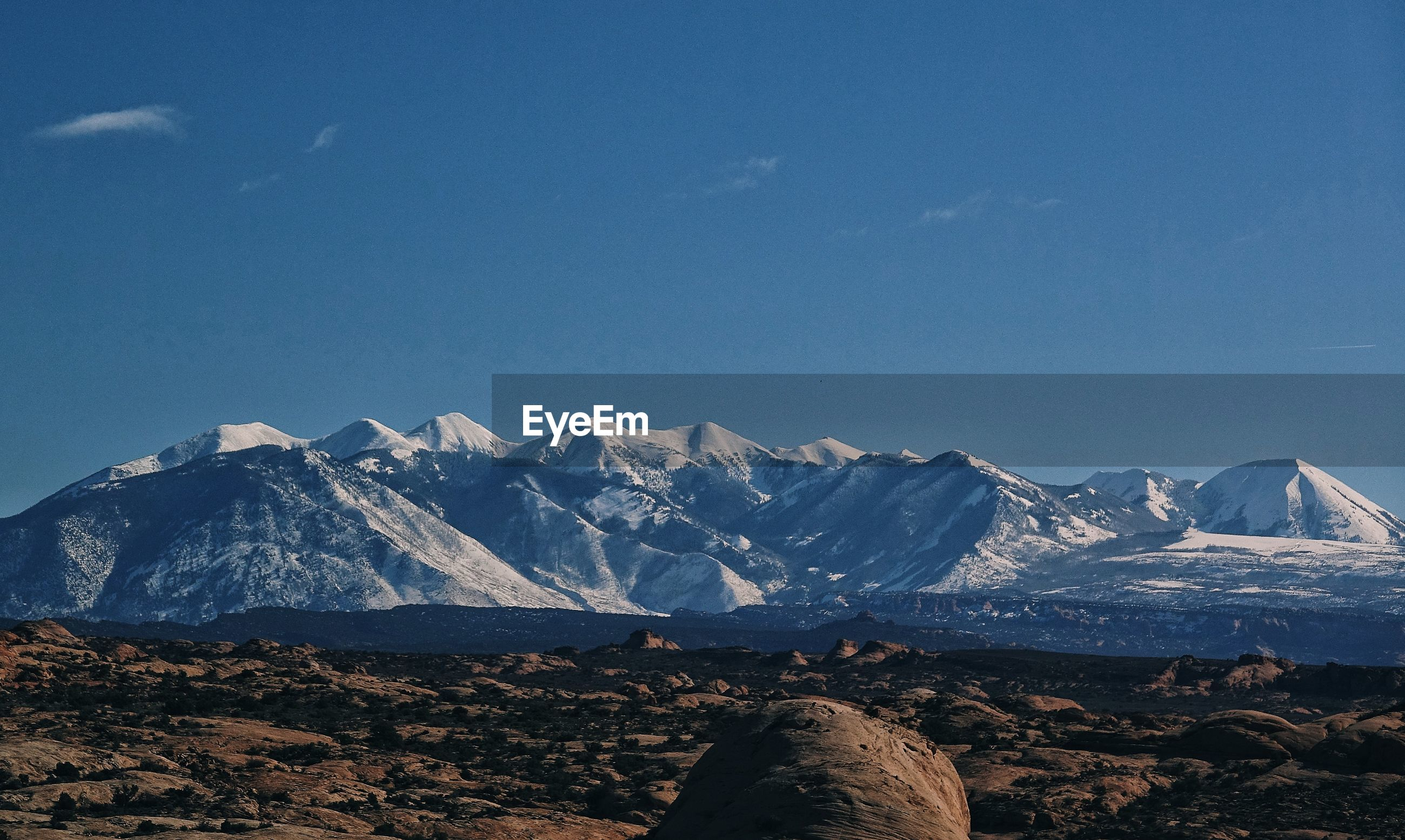 Scenic view of snowcapped mountains against sky at arches national park
