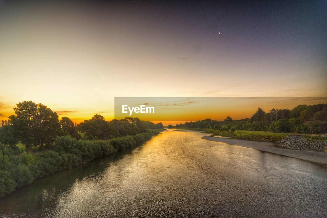 Scenic View Of River Amidst Trees Against Sky During Sunset