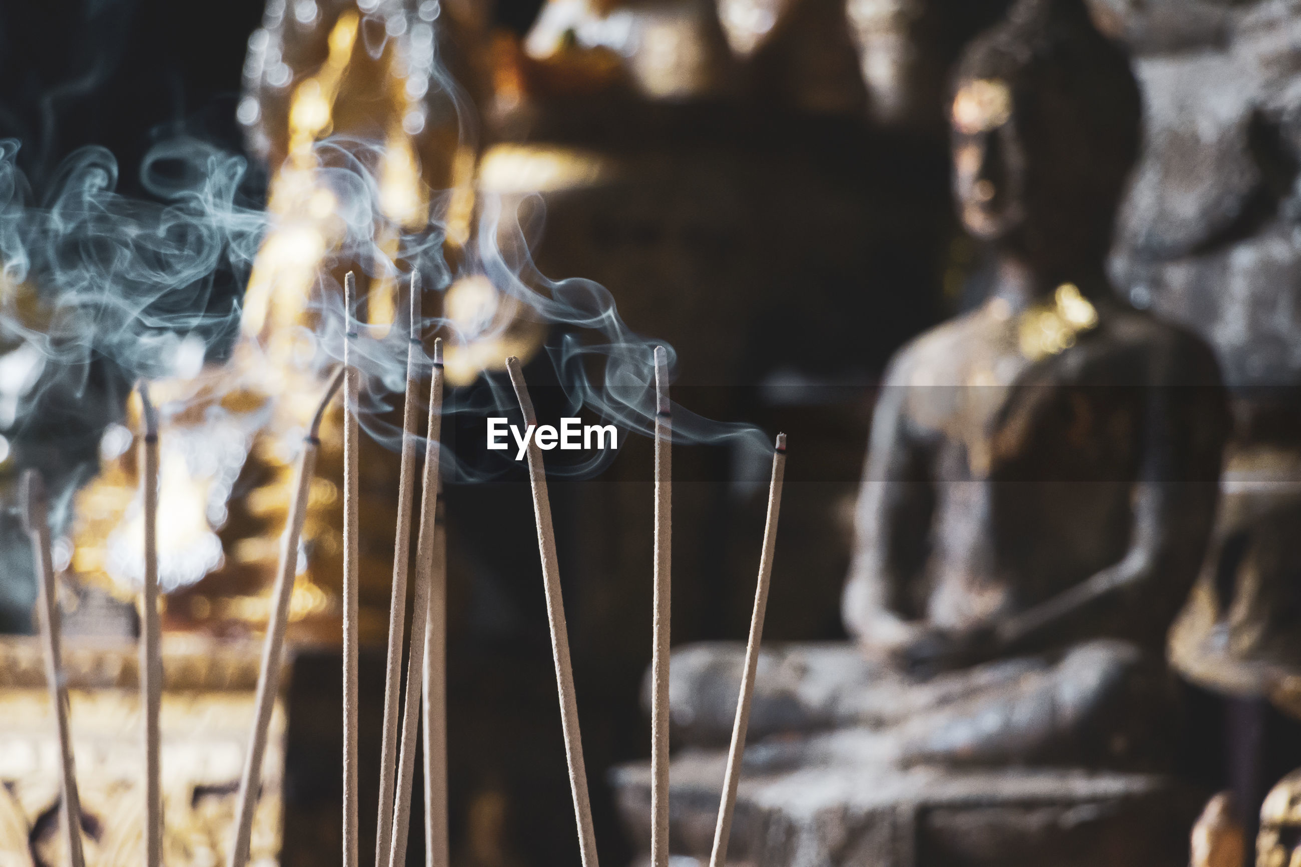 Close-up of incense sticks against statue