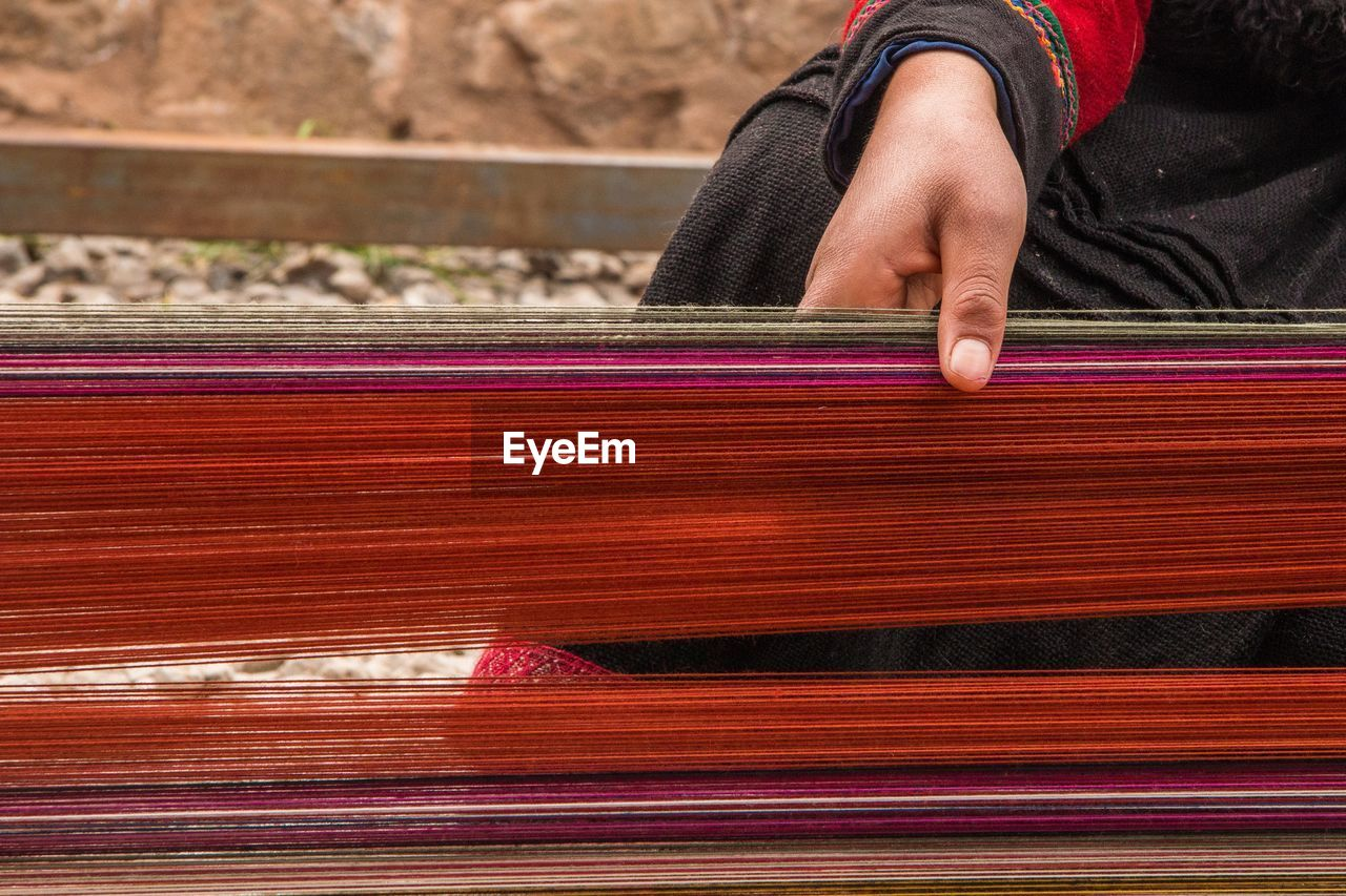 Cropped Image Of Woman Weaving Thread