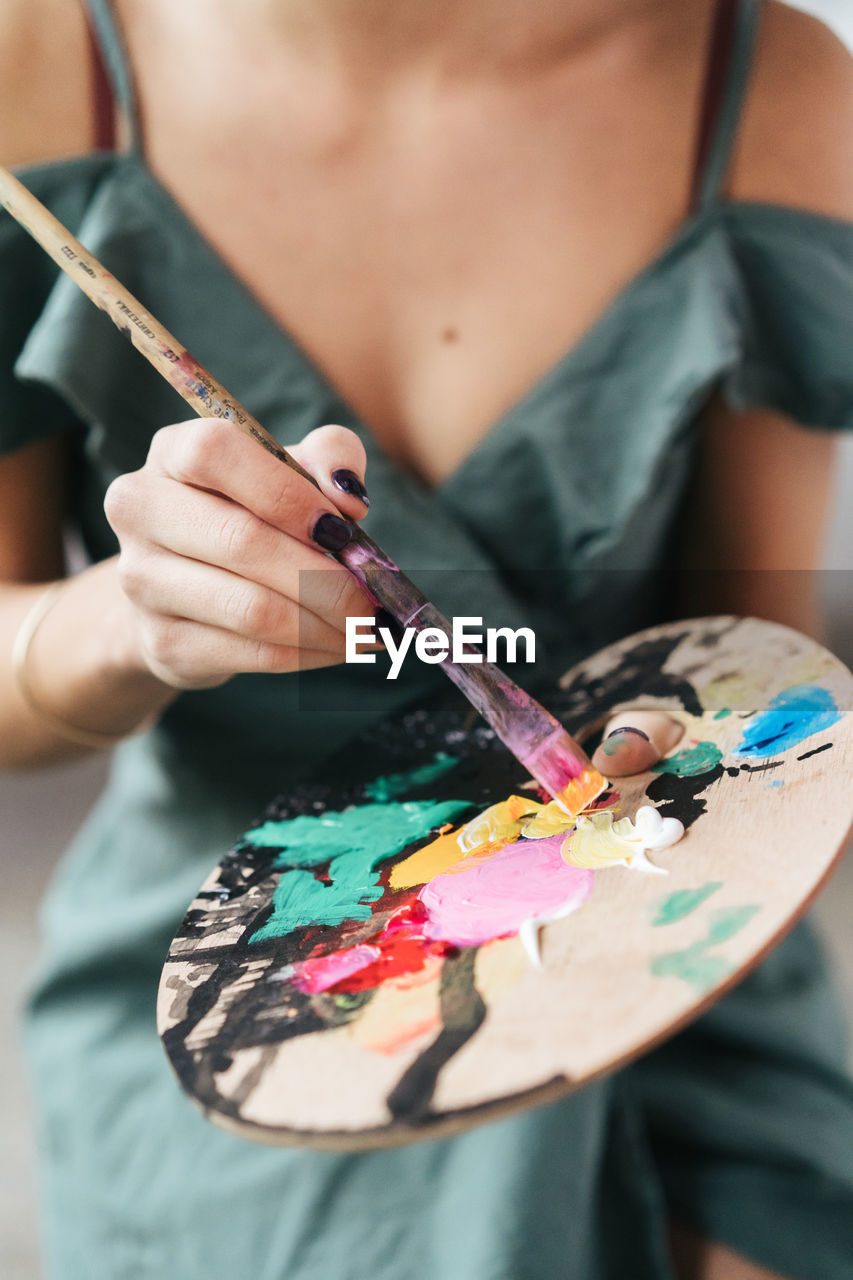 Midsection Of Painter Holding Messy Colorful Palate