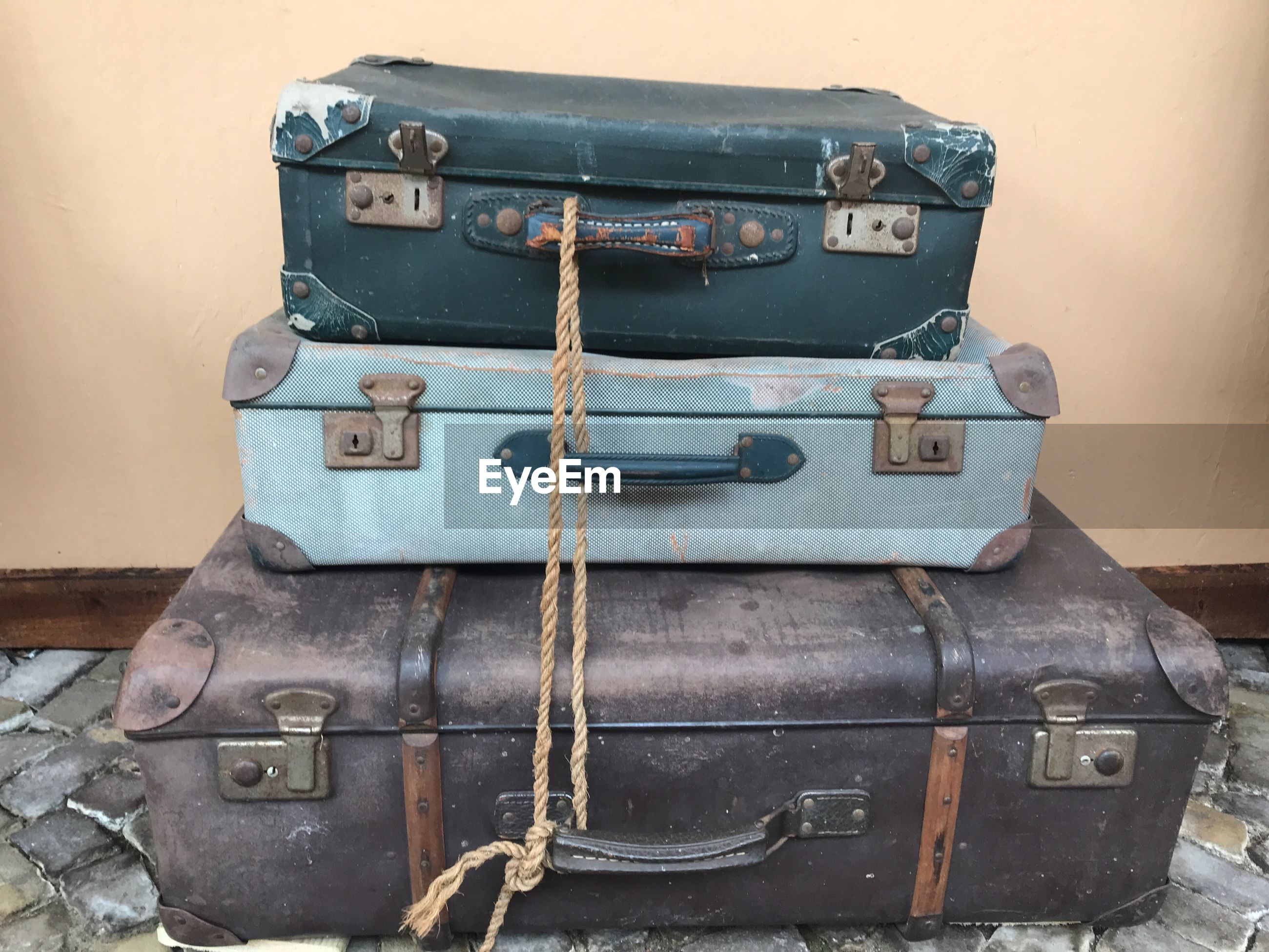 Close-up of old suitcases against wall