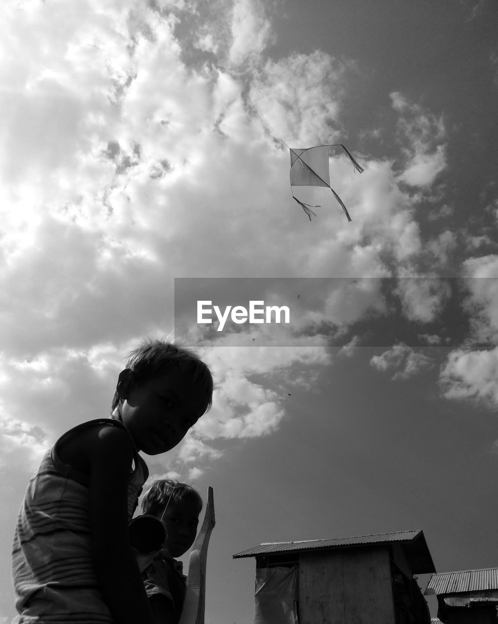 cloud - sky, sky, real people, one person, lifestyles, leisure activity, nature, low angle view, men, child, day, childhood, boys, outdoors, males, flying, casual clothing, standing, kite - toy