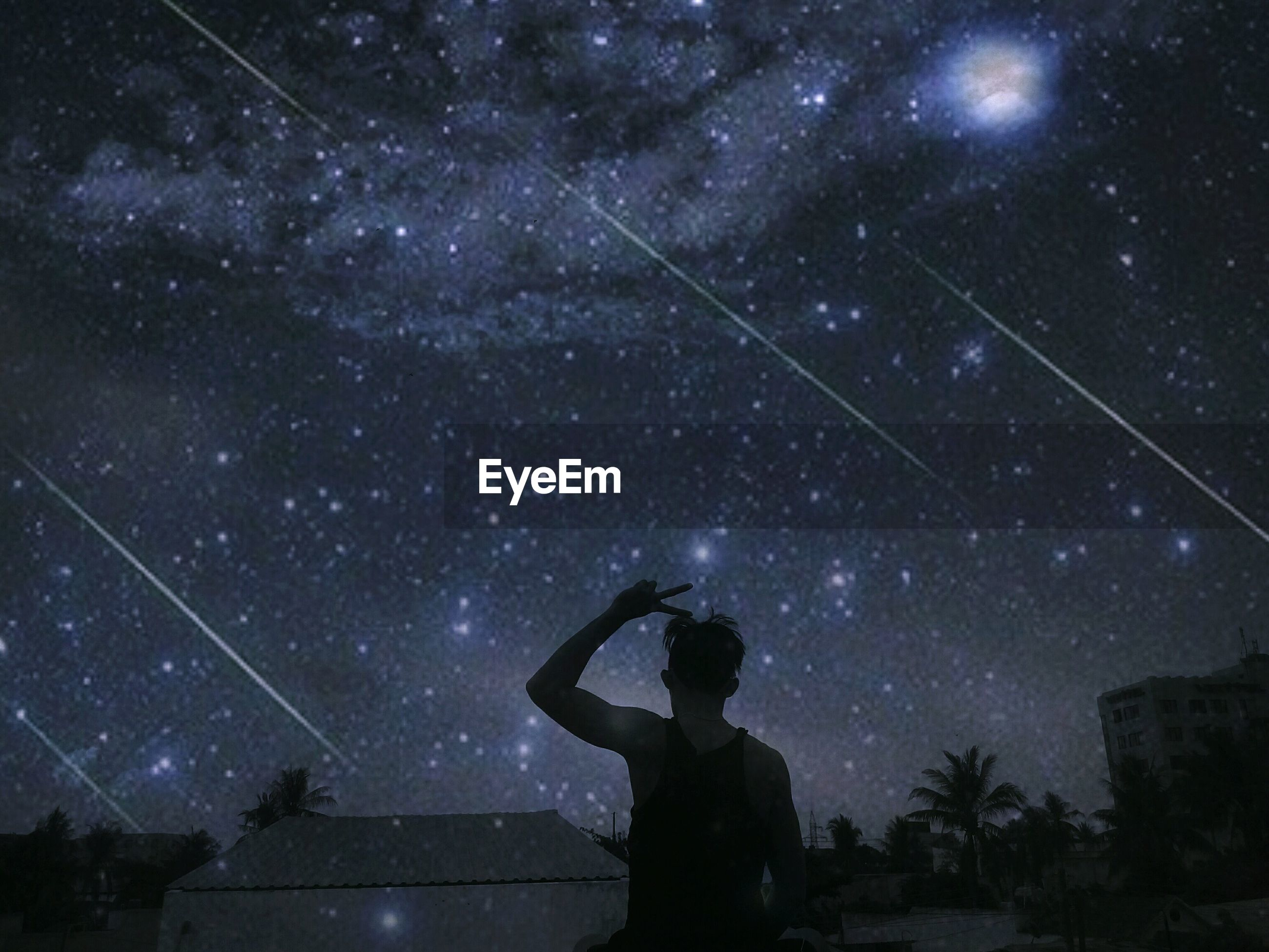 Rear view of man gesturing against starry sky at night