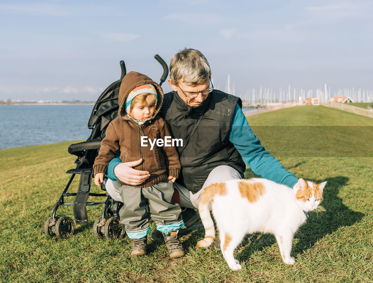 Mature Man With Granddaughter And Cat On Field
