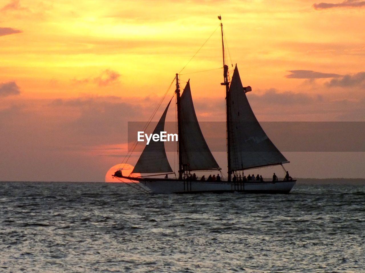Silhouette sailboat sailing on sea against orange sky