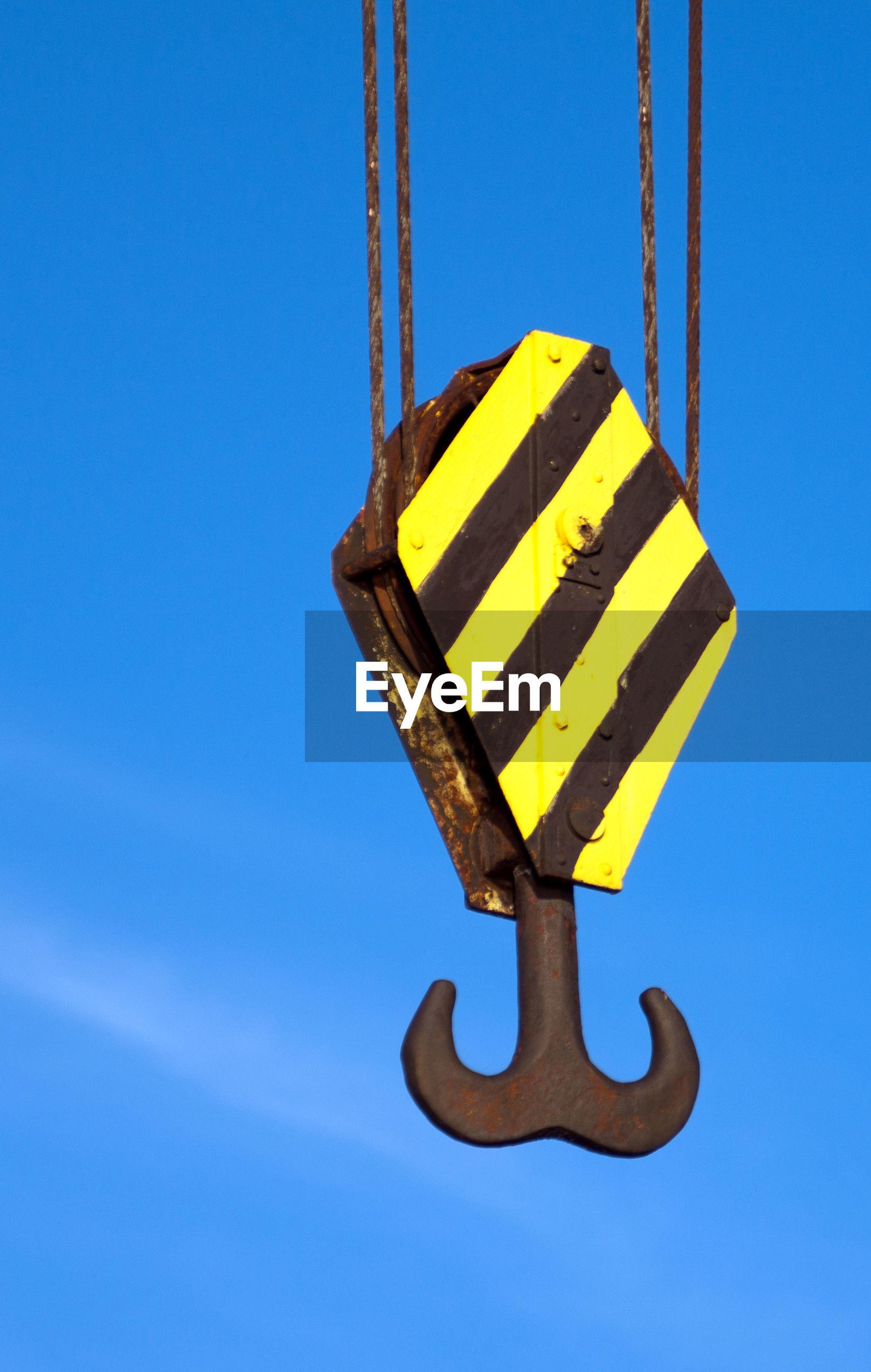 Hook of crane against blue sky