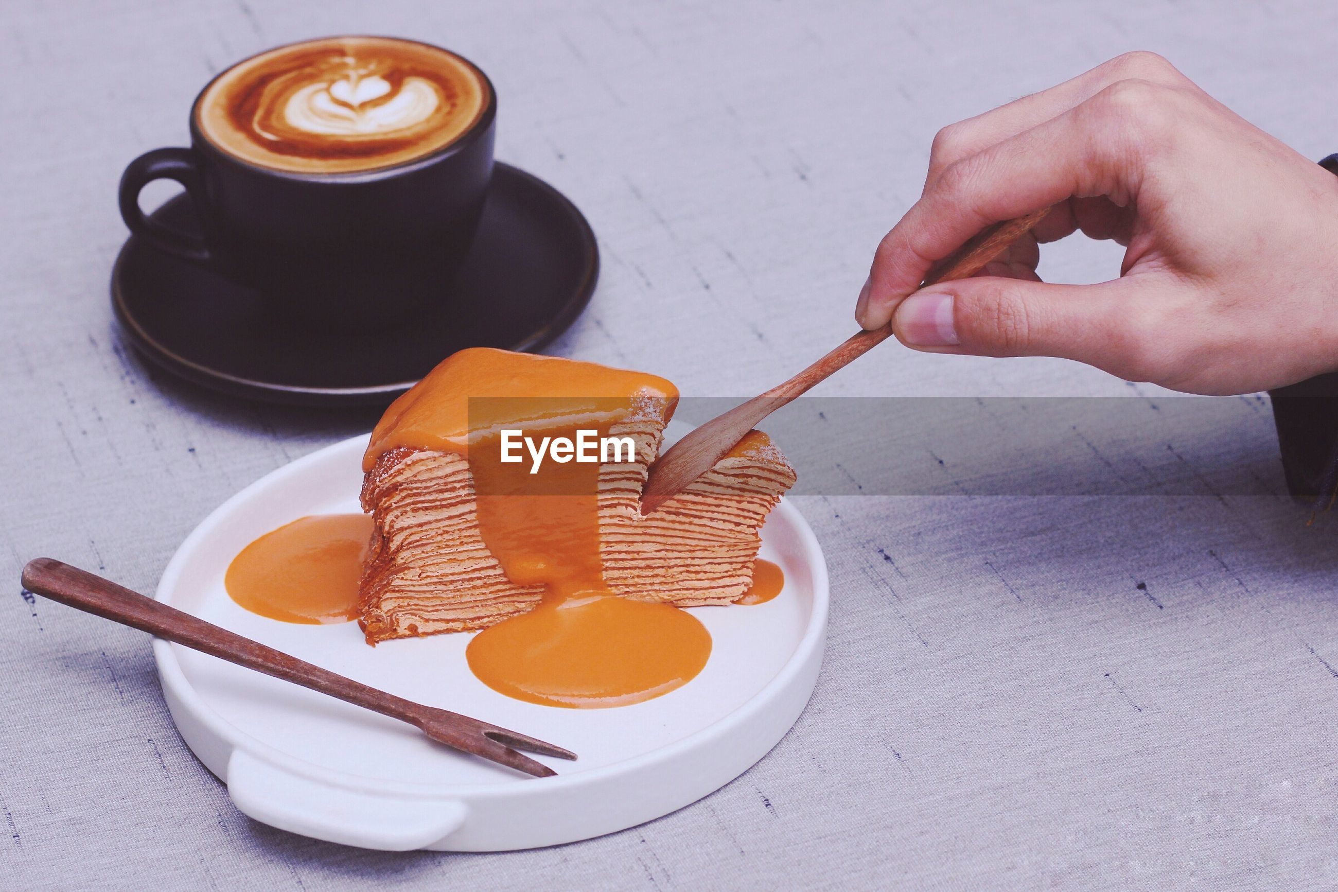 Cropped image of hand cutting dessert with spoon