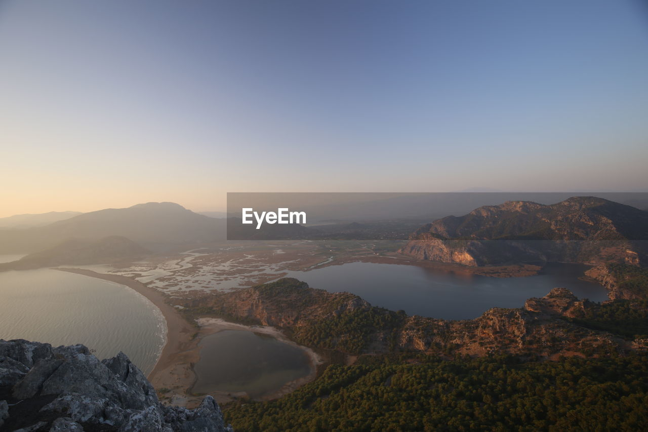Scenic View Of River By Mountains Against Clear Sky