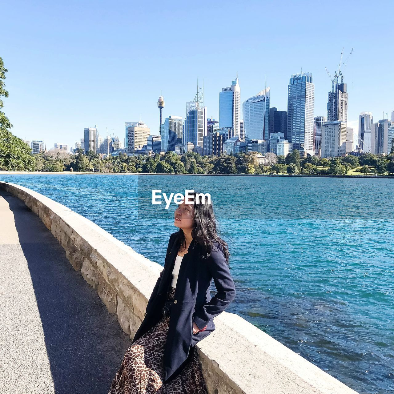 Woman by sea against modern buildings in city
