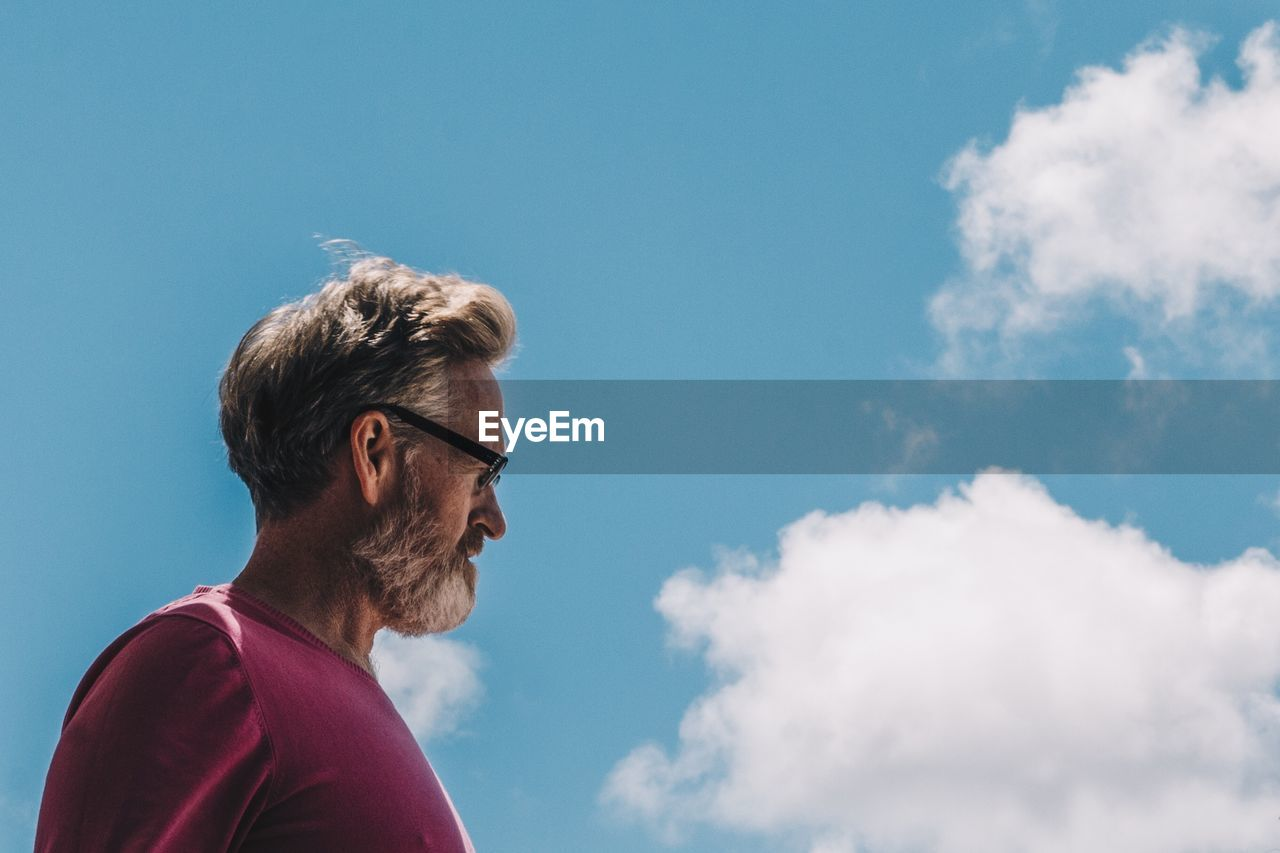 sky, cloud - sky, glasses, blue, low angle view, lifestyles, eyeglasses, real people, one person, nature, headshot, day, leisure activity, facial hair, beard, side view, adult, portrait, looking, outdoors, hairstyle
