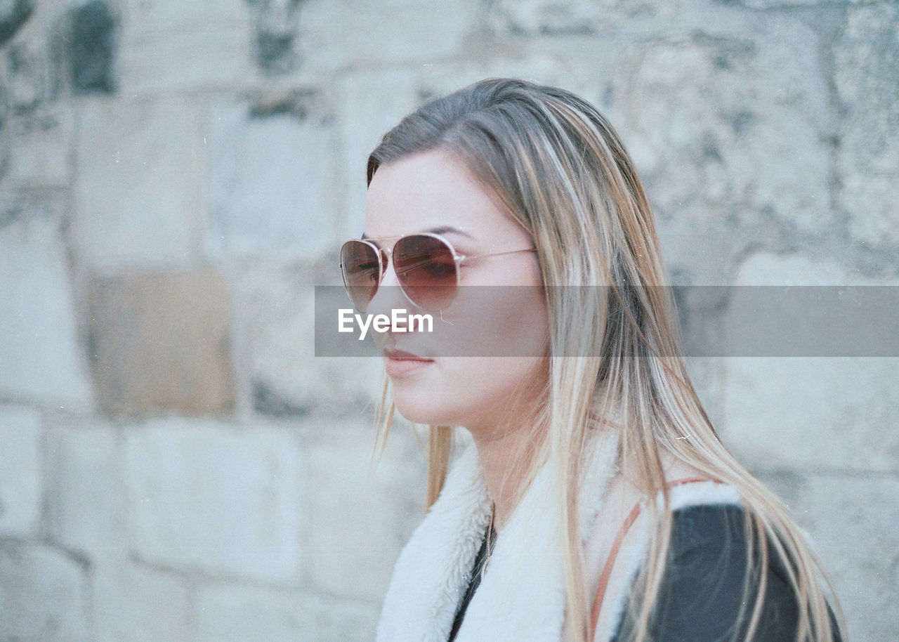 Young Woman Wearing Sunglasses By Wall