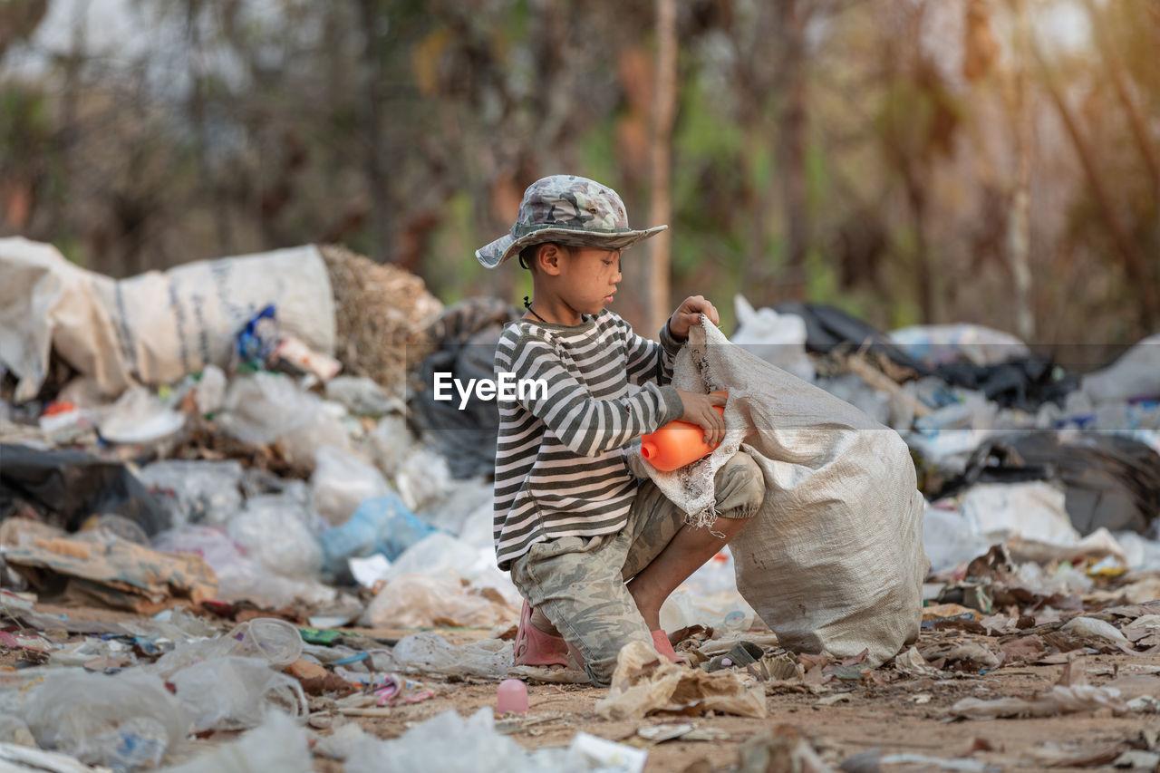 Boy wearing hat collecting garbage